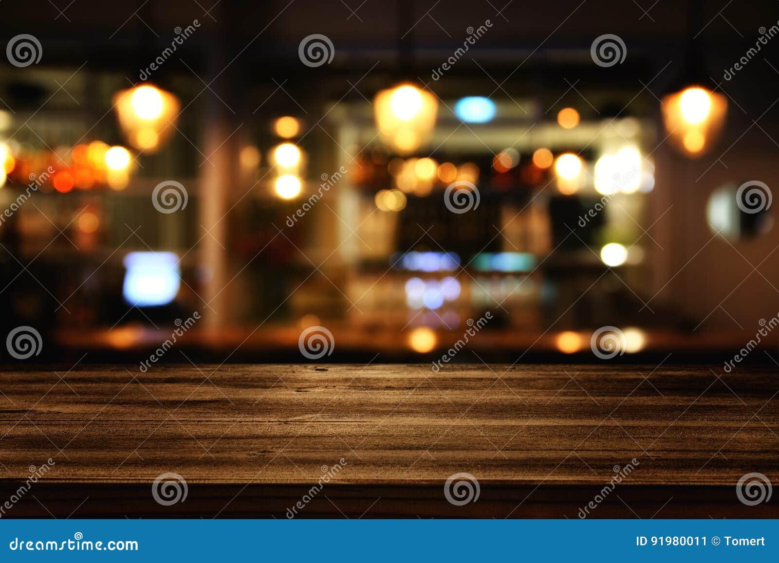 Tabla de madera delante de luces borrosas extracto del restaurante