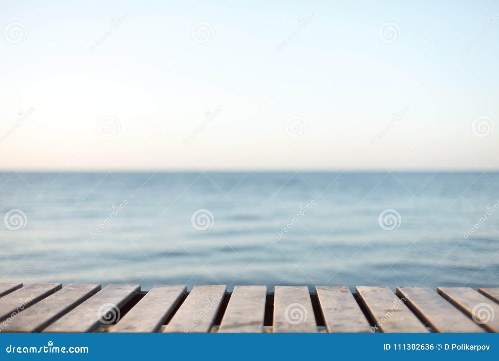 Tabla de madera delante del fondo borroso del mar