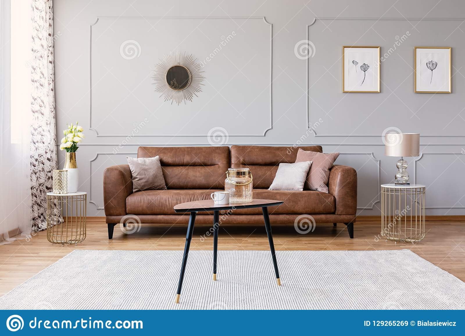 Tabla de madera en la alfombra delante del sofá de cuero en interior plano gris con los carteles y el espejo