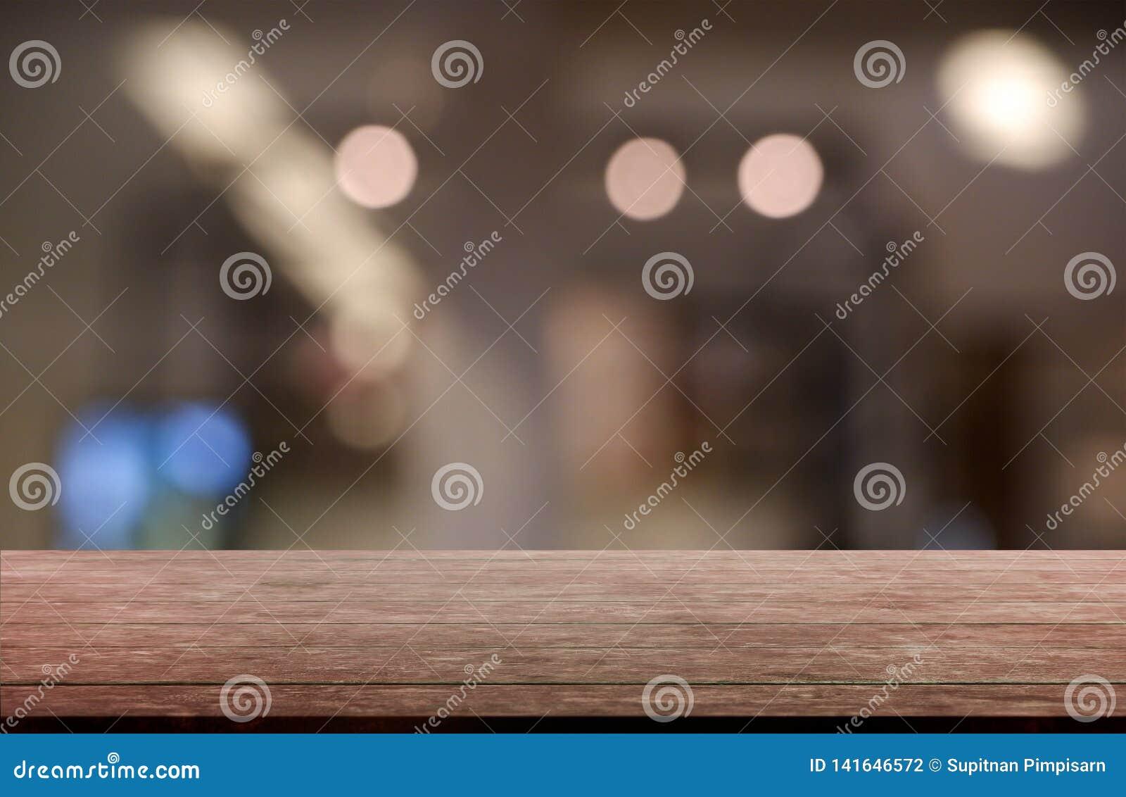 Tabla de madera vacía delante del fondo borroso abstracto del interior del restaurante, del café y de la cafetería puede ser util