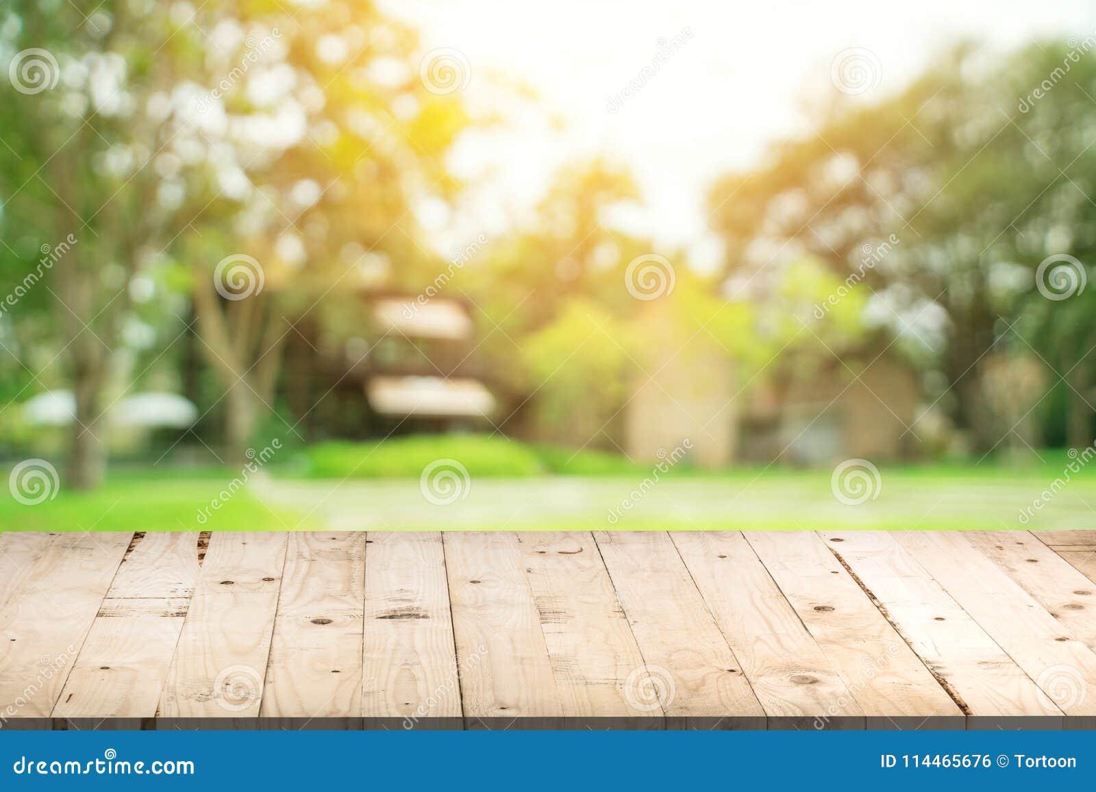 Tabla de madera vacía y fondo defocused del bokeh y de la falta de definición de Gard