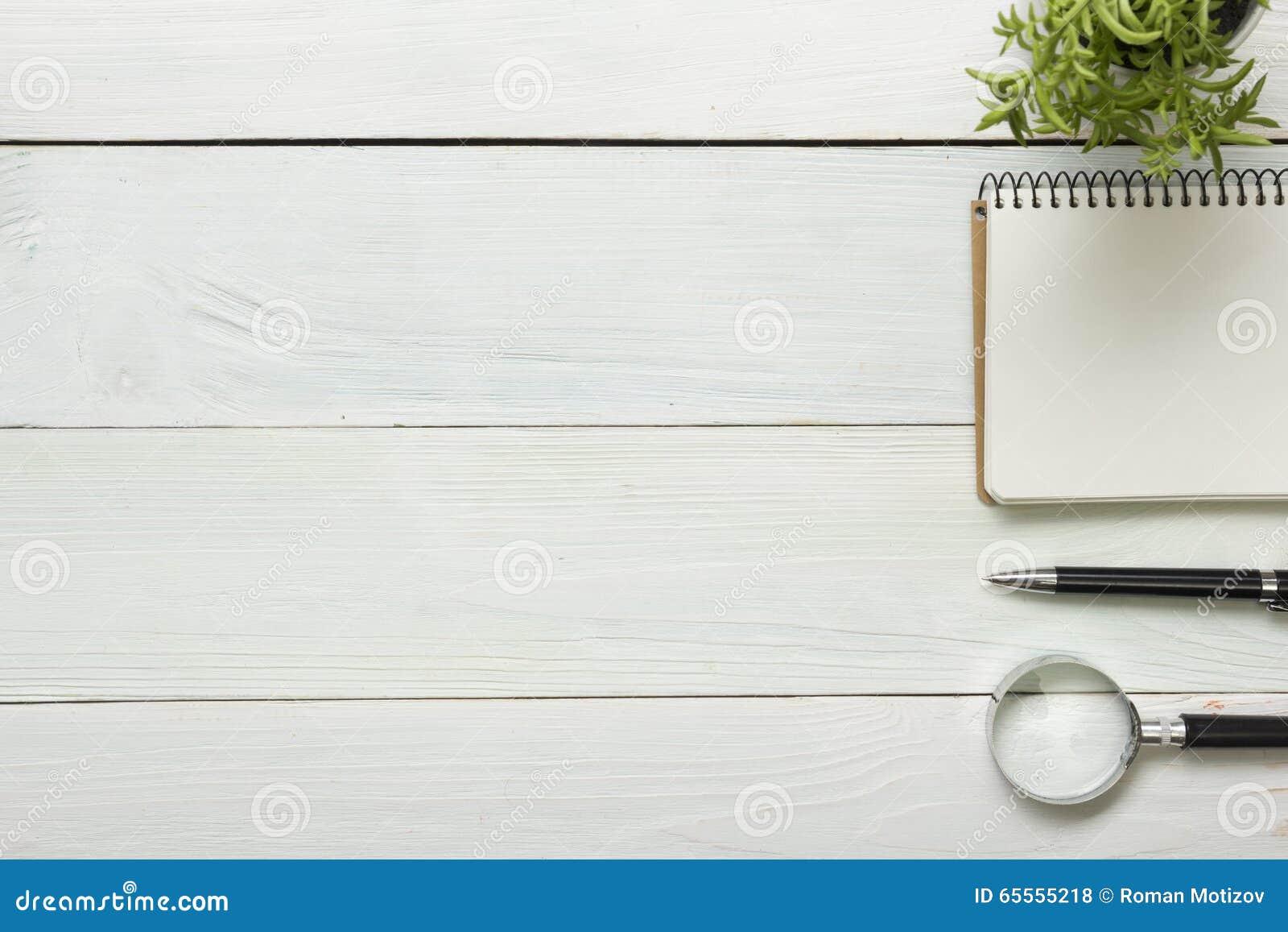 Tabla del escritorio de oficina con las fuentes Visión superior Copie el espacio para el texto Libreta, pluma, lupa, flor