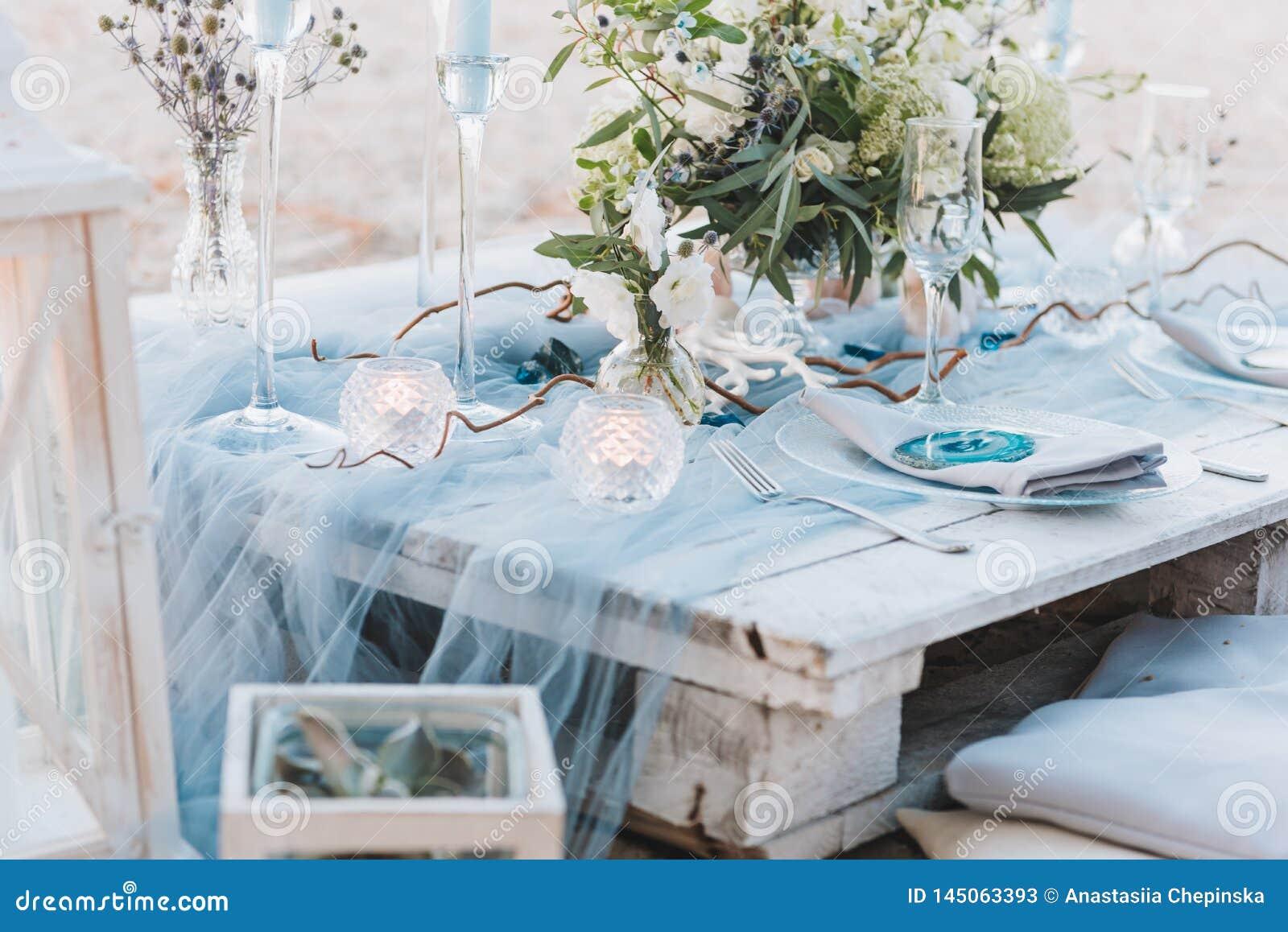 Tabla elegante puesta en los pasteles azules para una boda de playa