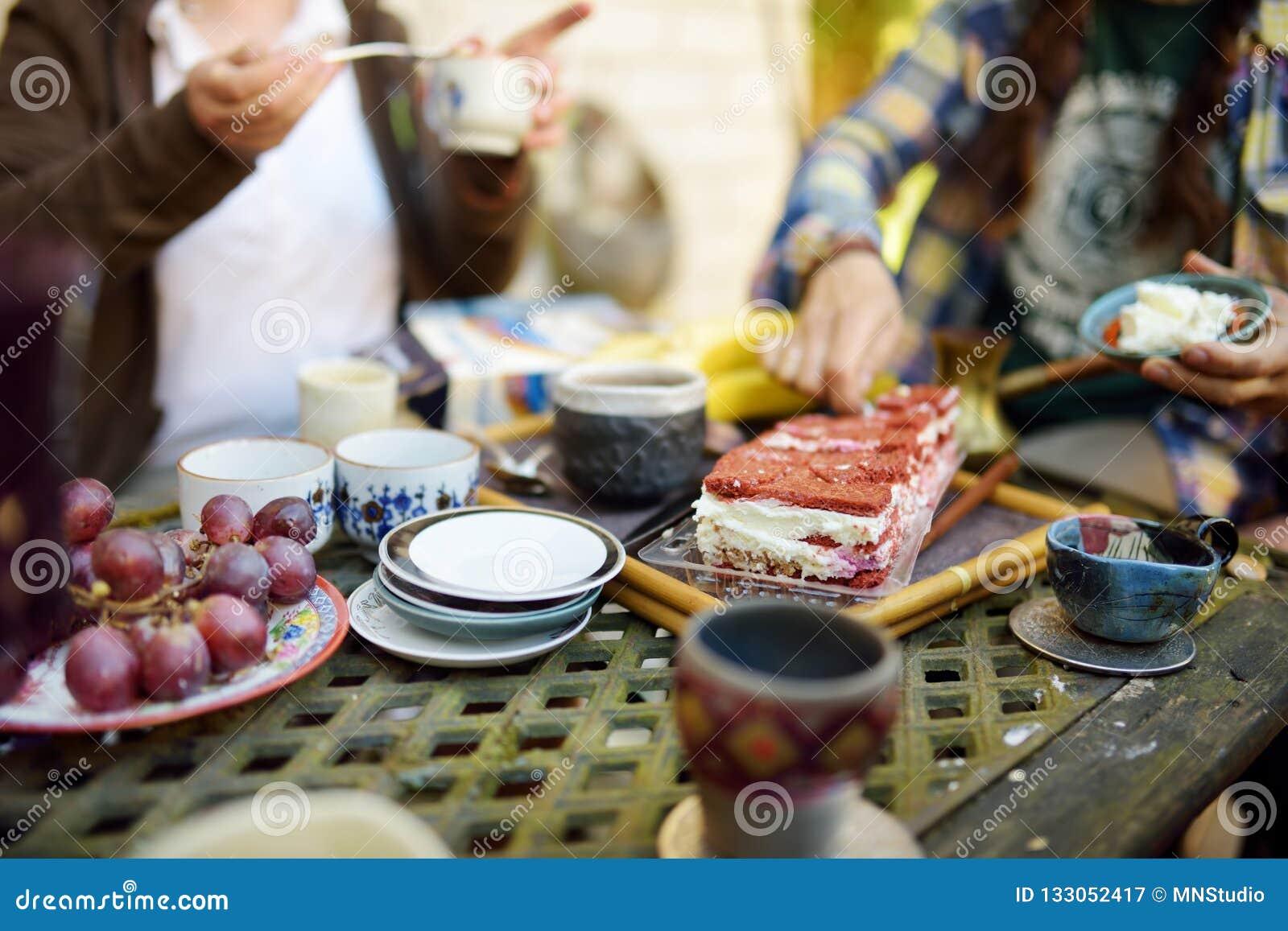 Tabla hermosa del postre con las tazas de cerámica coloridas, los platillos, la torta de zanahoria deliciosa y las frutas Consumi