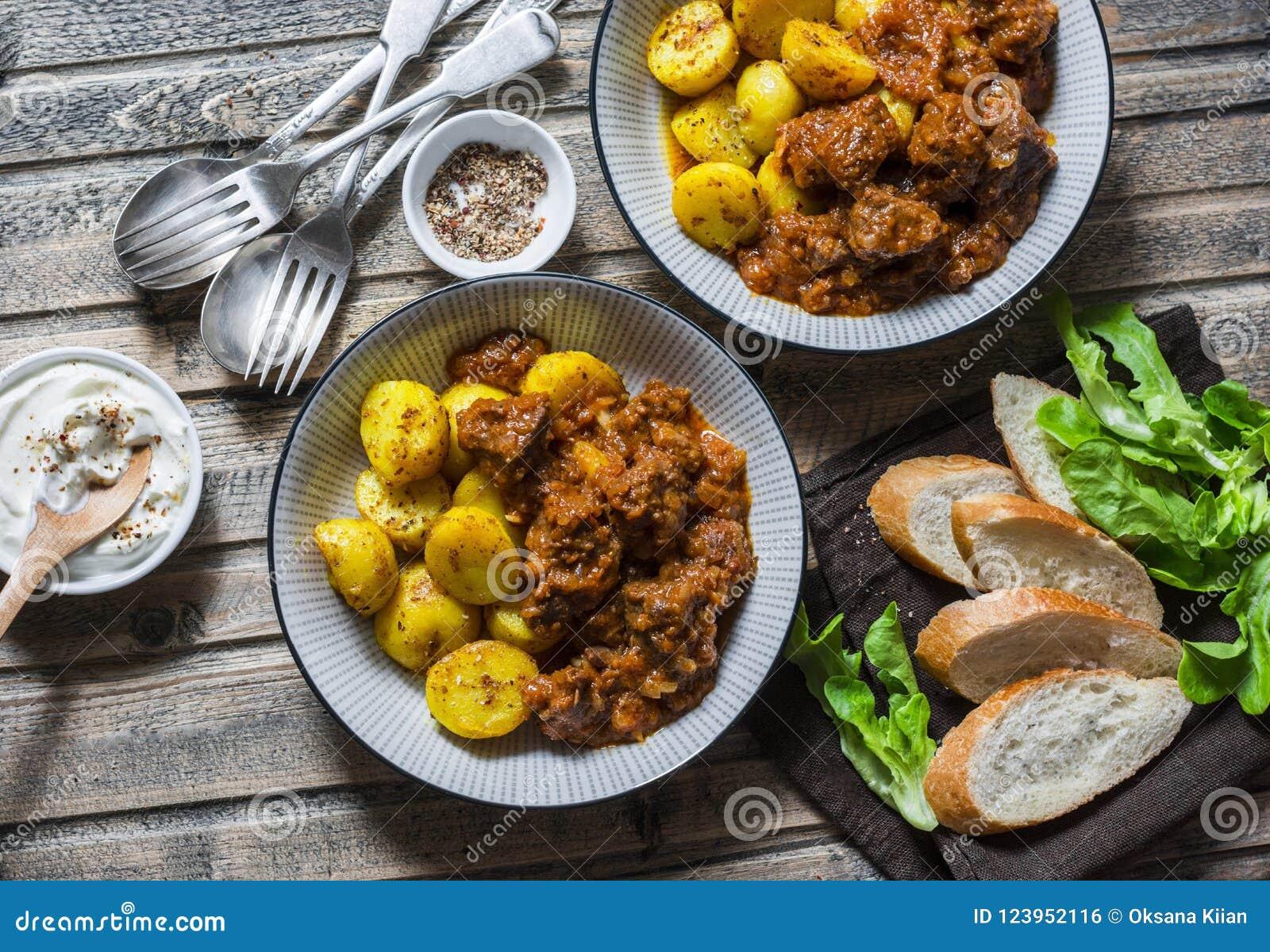 Tabla servida del almuerzo - caldo de buey irlandés con las patatas de la cúrcuma de Bombay Comida estacional deliciosa en un fon