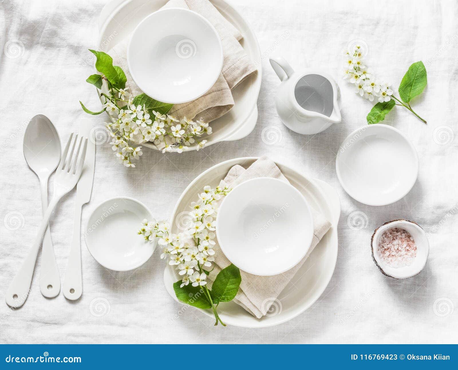 Tabla vacía servida con la loza blanca, flores, servilletas en el fondo blanco, visión superior Tabla casera acogedora de la comi