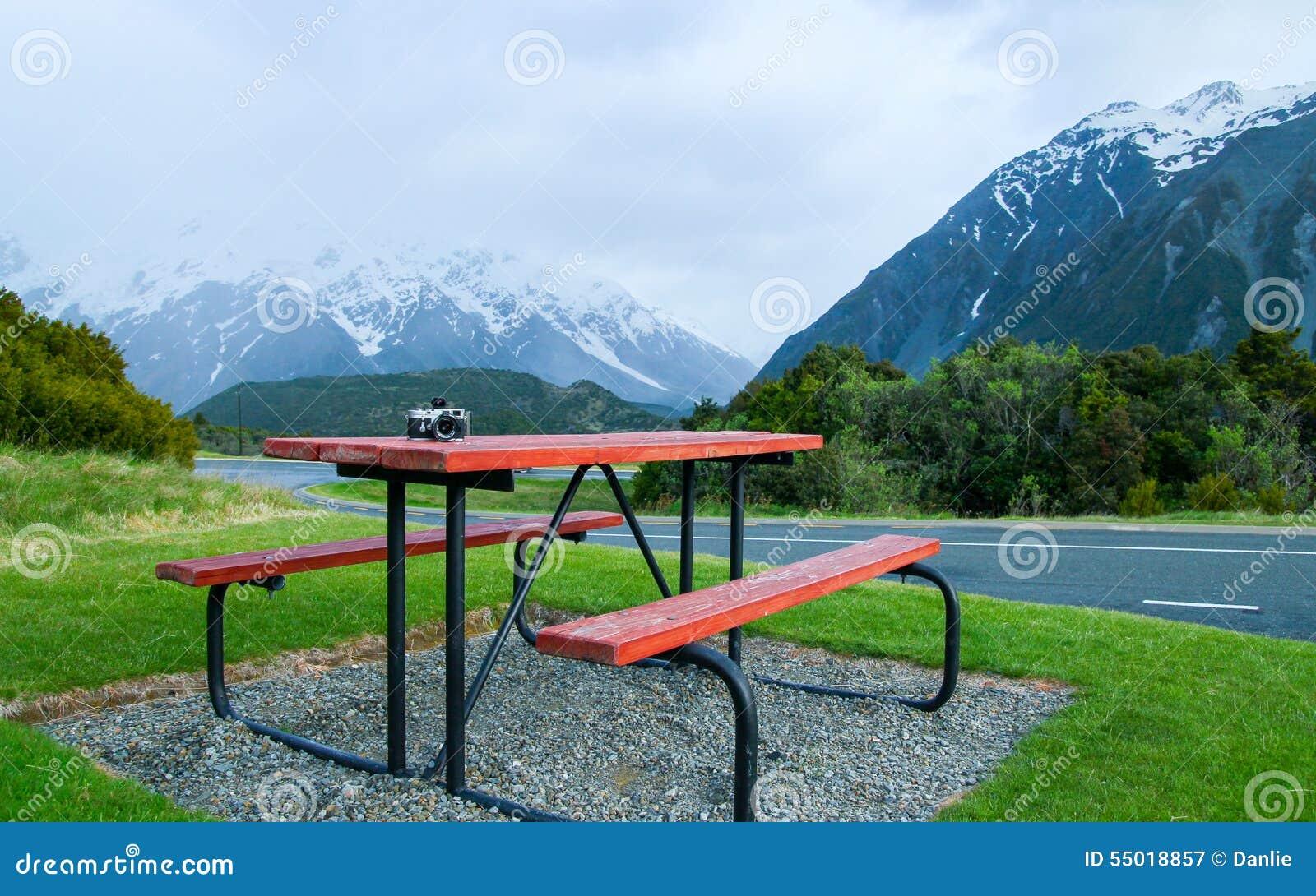 Tabla y banco de invitación en el pie de montañas de la nieve