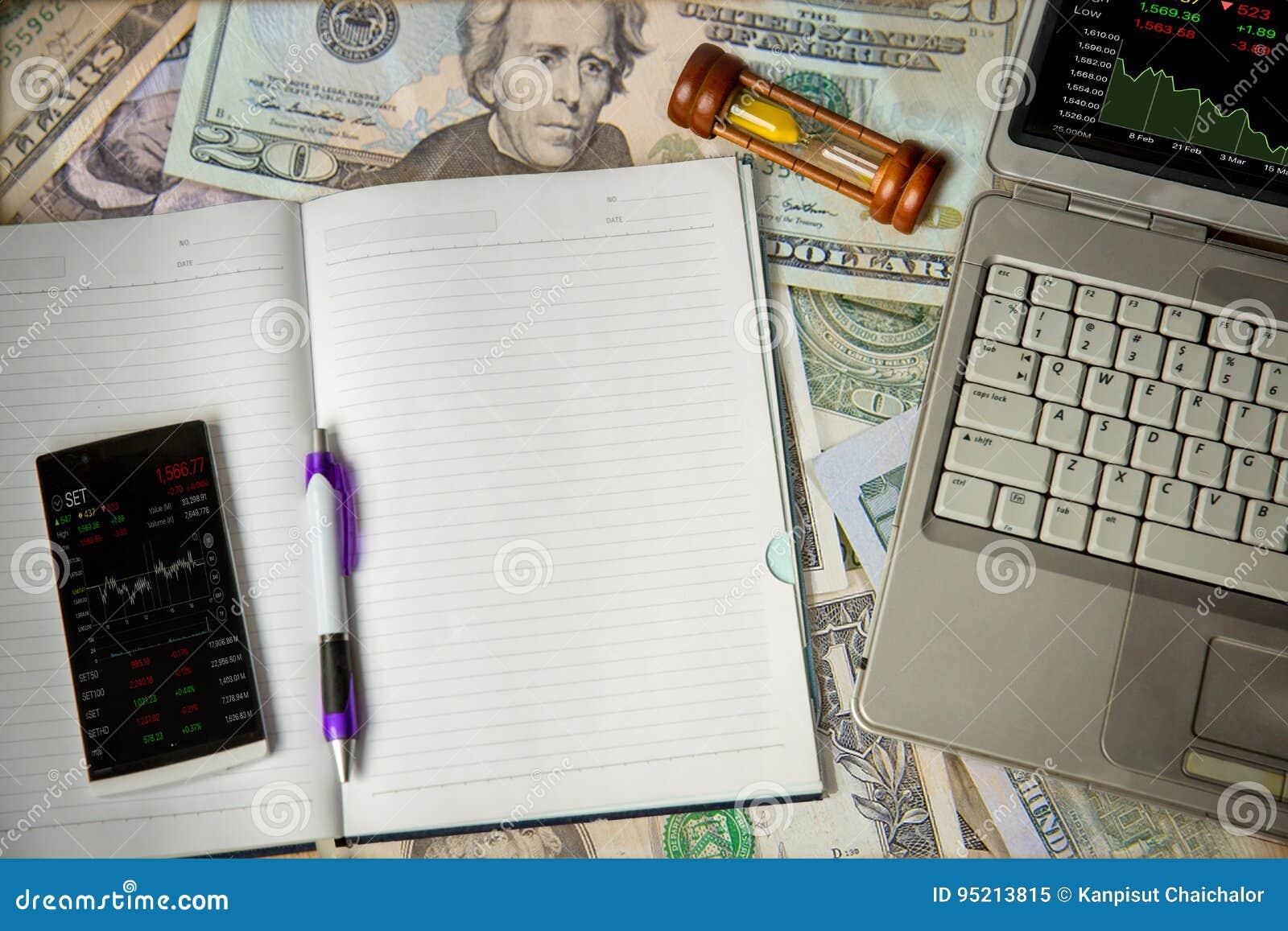 Tabla y pluma móviles del precio del mercado libre en aislante del cuaderno en los billetes de dólar fondo, tabla del precio del