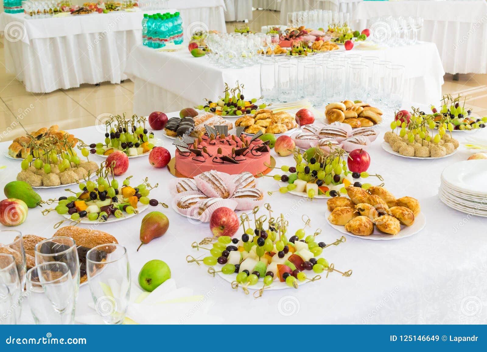Tablas servidas en el banquete Postres, fruta y pasteles en la comida fría Cristalería y botellas de agua minerales Rosas en un j