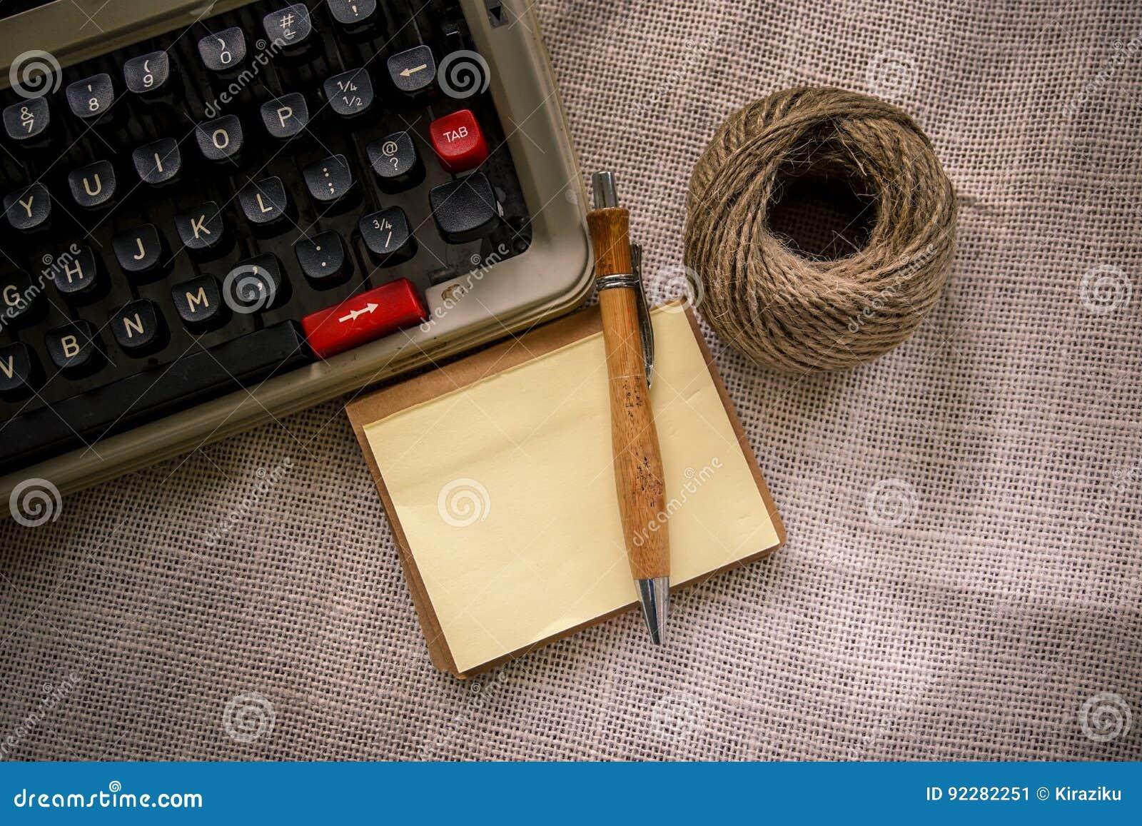 Table blanche de bureau avec la vieux machine à écrire cordes