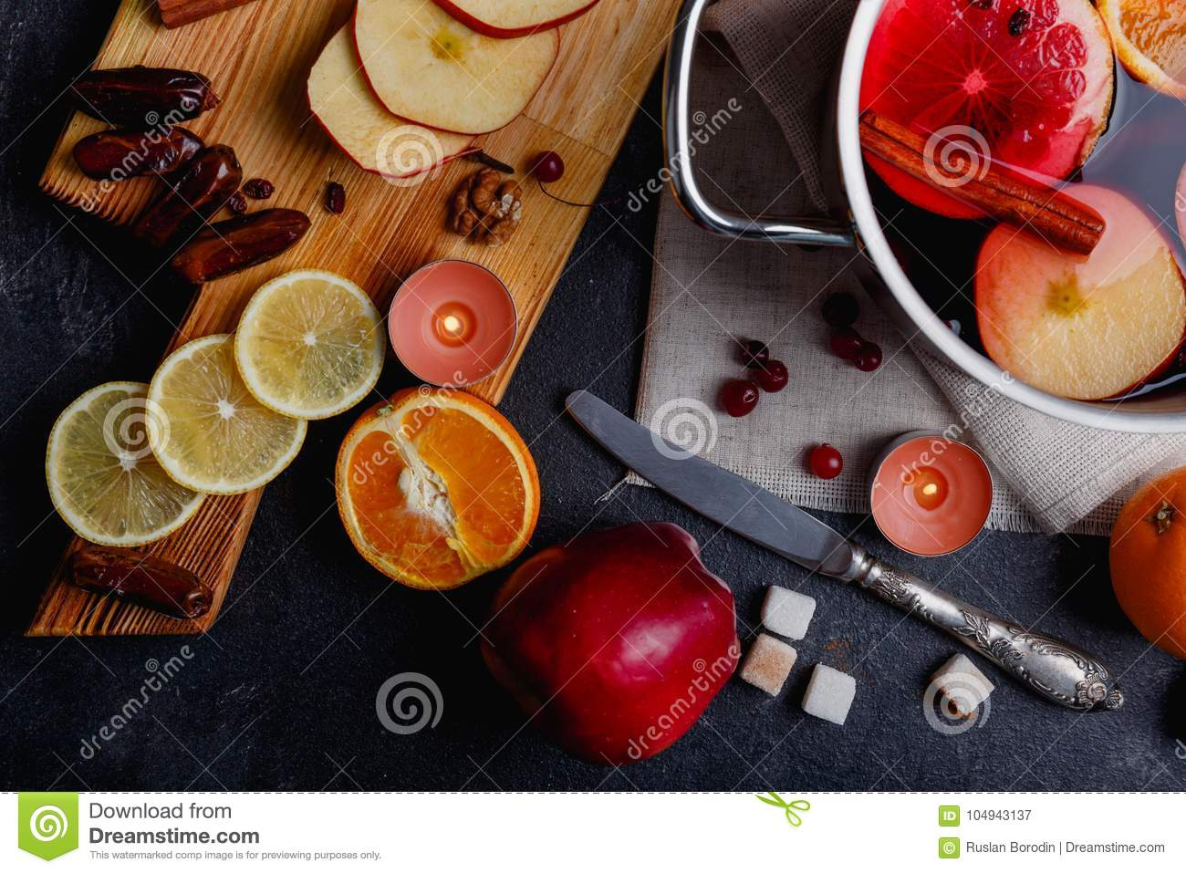 On a table is a board with dates and slices of apples and lemon, a knife and a pan with a mulled wine. View from above.