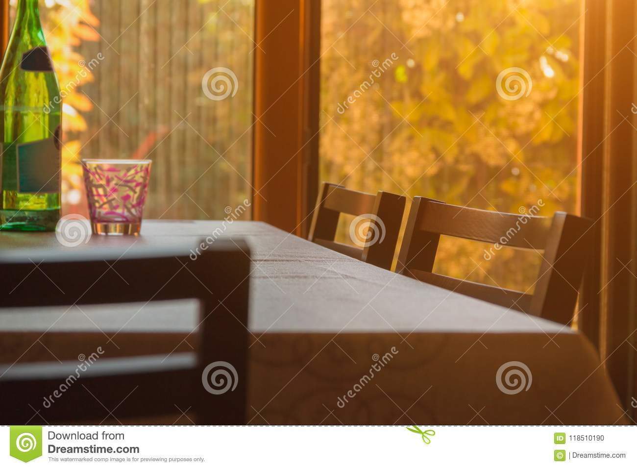 A table with chairs stands in front of a window in which the sun shines, home architecture, home comfort, artistic background