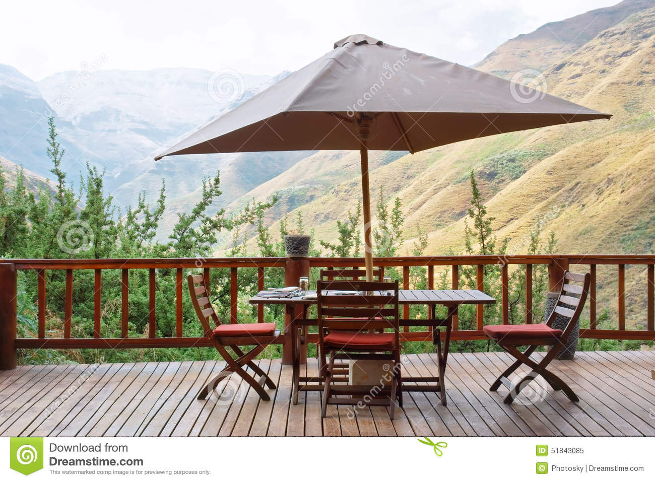 Table and chairs under umbrella on terrace against awesome mount