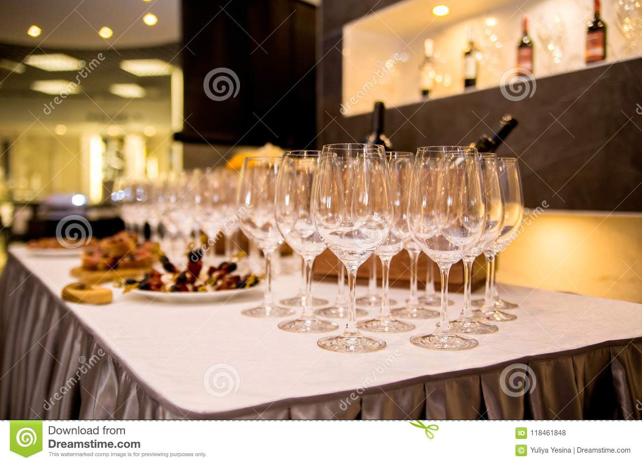 The table is covered with appetizers and glasses for wine