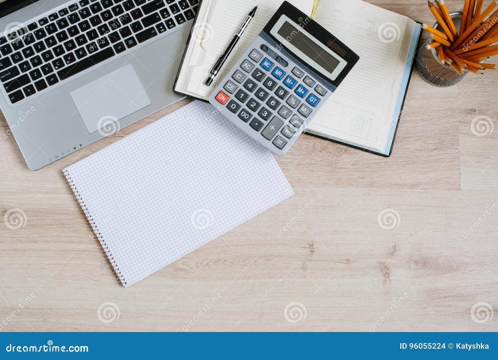 Table de bureau avec l ordinateur, les approvisionnements et la calculatrice Vue supérieure avec l espace de copie