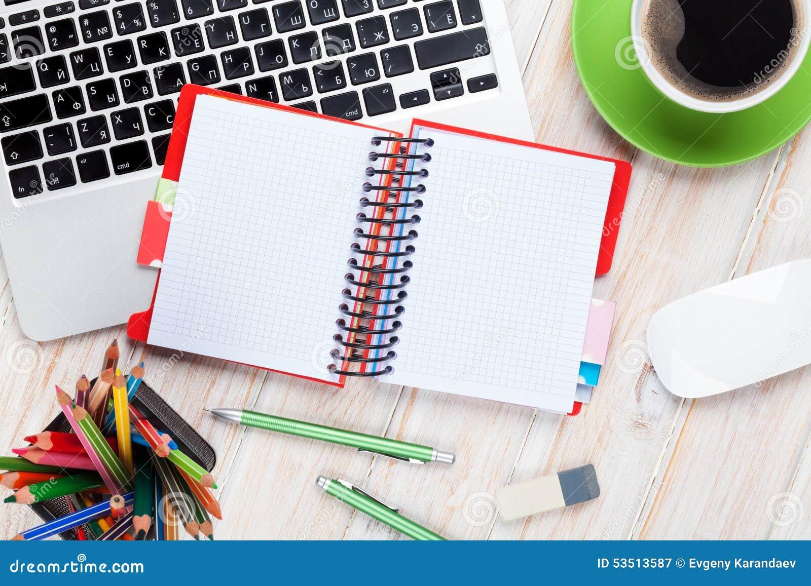 Table de bureau avec l ordinateur, les approvisionnements et la tasse de café