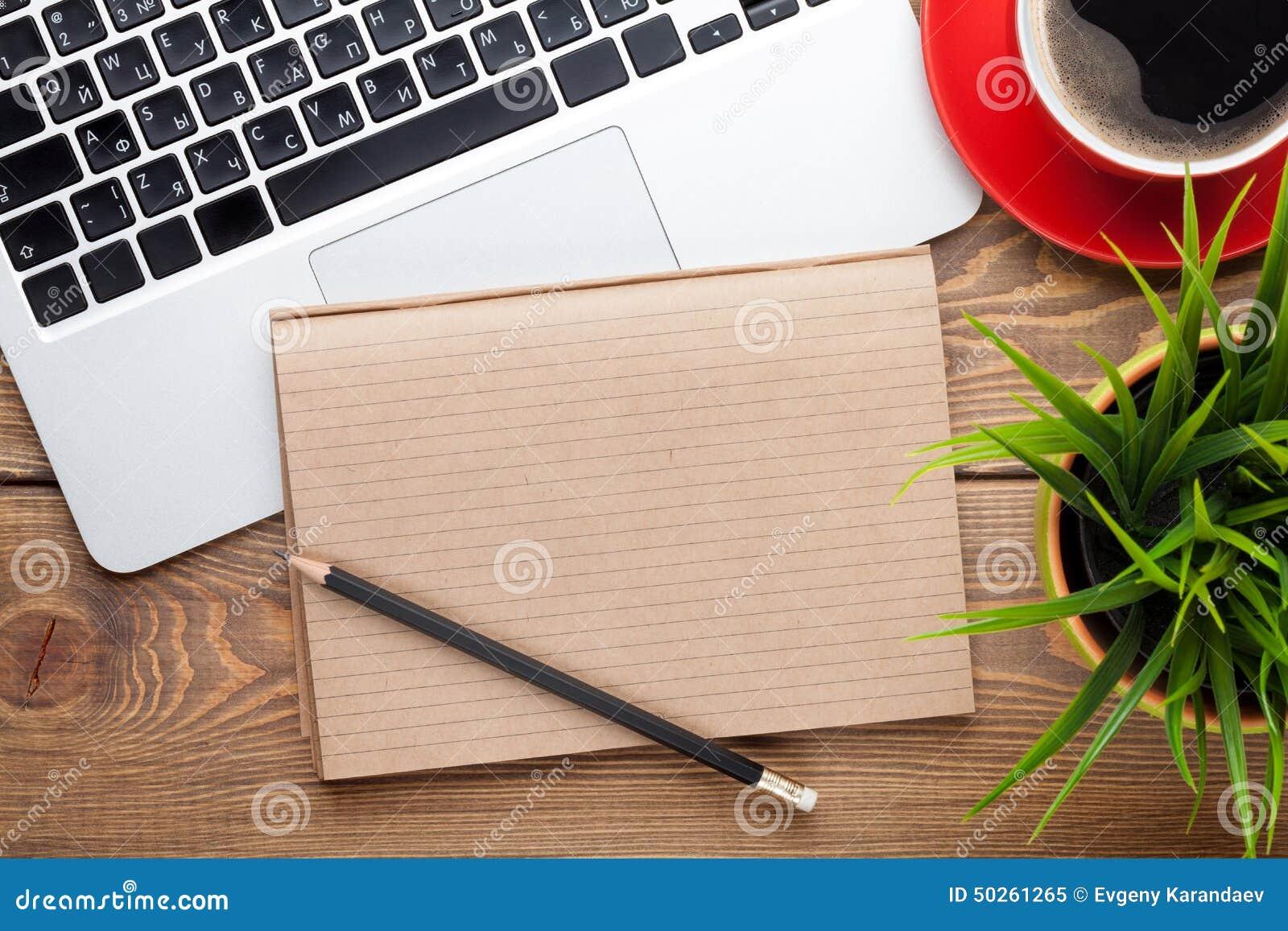 Table de bureau avec l ordinateur, les approvisionnements, la tasse de café et la fleur