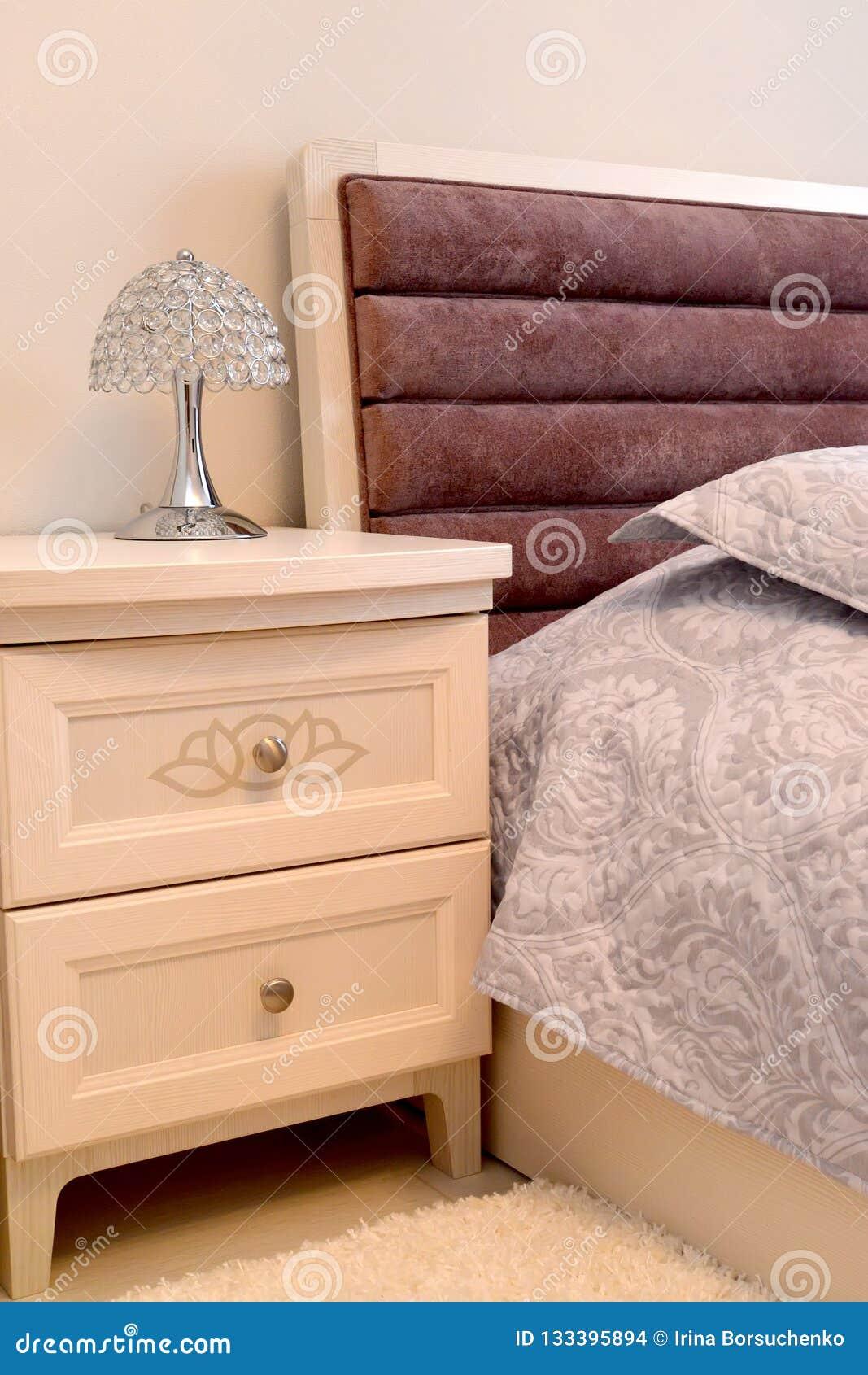 Table de chevet avec une lampe de bureau dans un intérieur de chambre à coucher Type scandinave