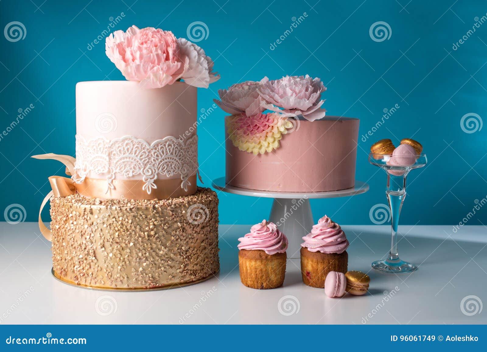 Table de luxe de mariage avec un beau gâteau rose décoré de la rose et de l or de rose de mastic sur un fond bleu