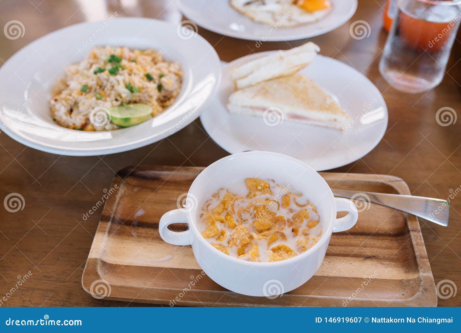 Table de petit déjeuner - placez de la céréale remplie du lait dans la cuvette et le plat en bois