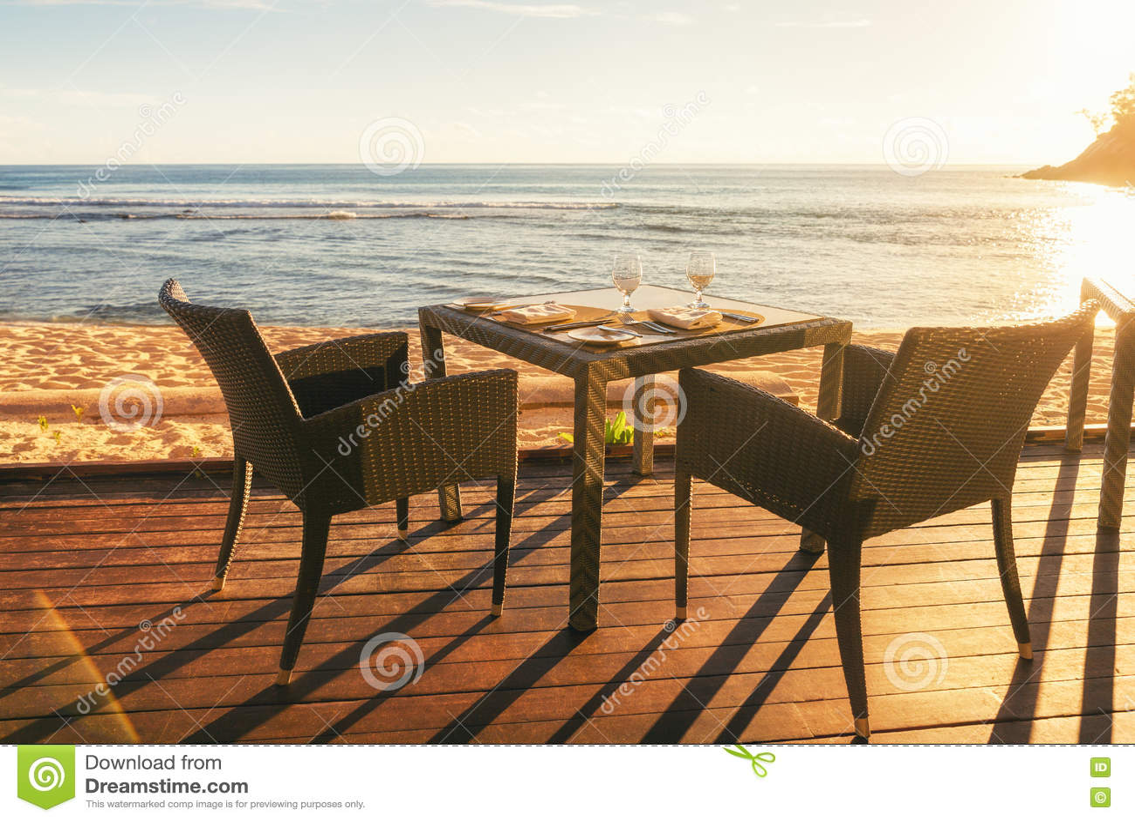 Table de salle à manger et deux chaises sur le decking par le côté de mer à égaliser le su