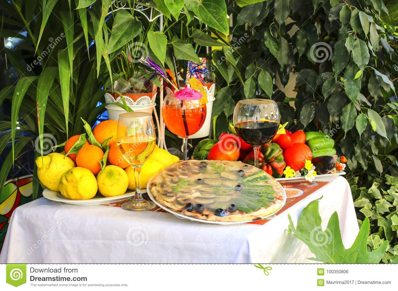 Table decorated with pizza, fruit and wine traditional Italian