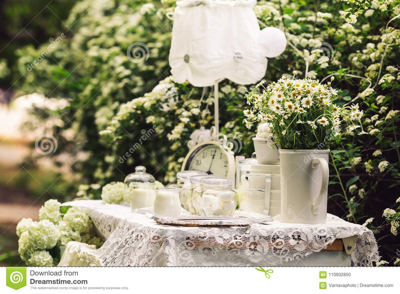 The table is decorated in white with old hours candles flowers download the table is decorated in white with old hours candles flowers daisies izmirmasajfo