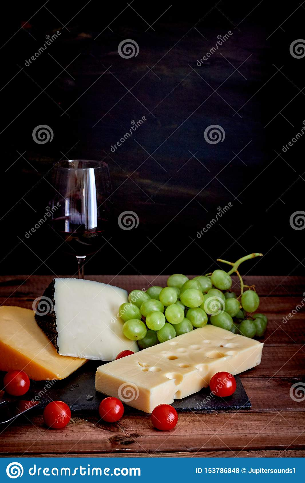 Table with different cheeses and wine glass on dark background