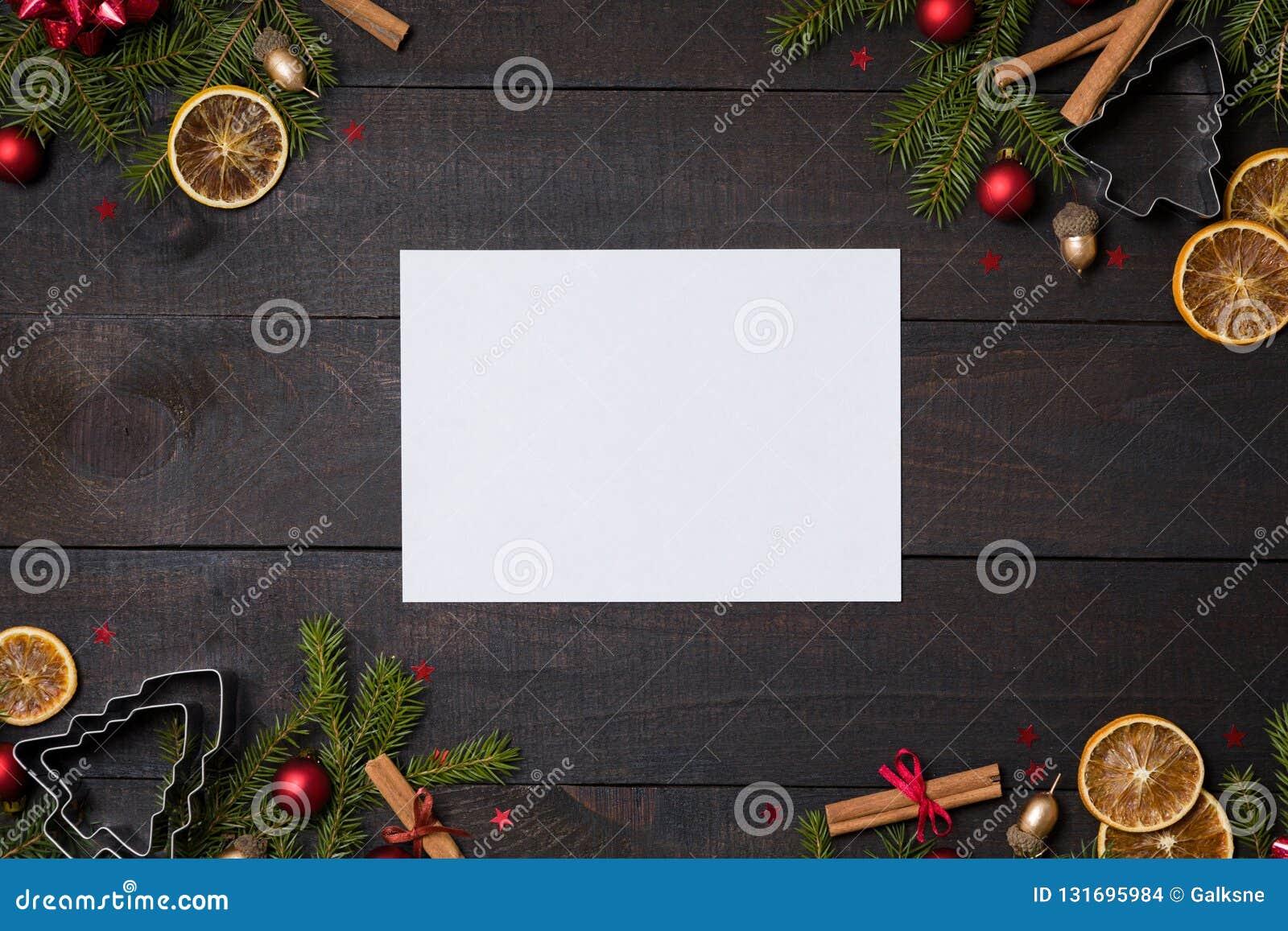 Table en bois rustique foncée flatlay - fond clair de Noël de cartes de note avec le cadre de branche de décoration et de sapin V