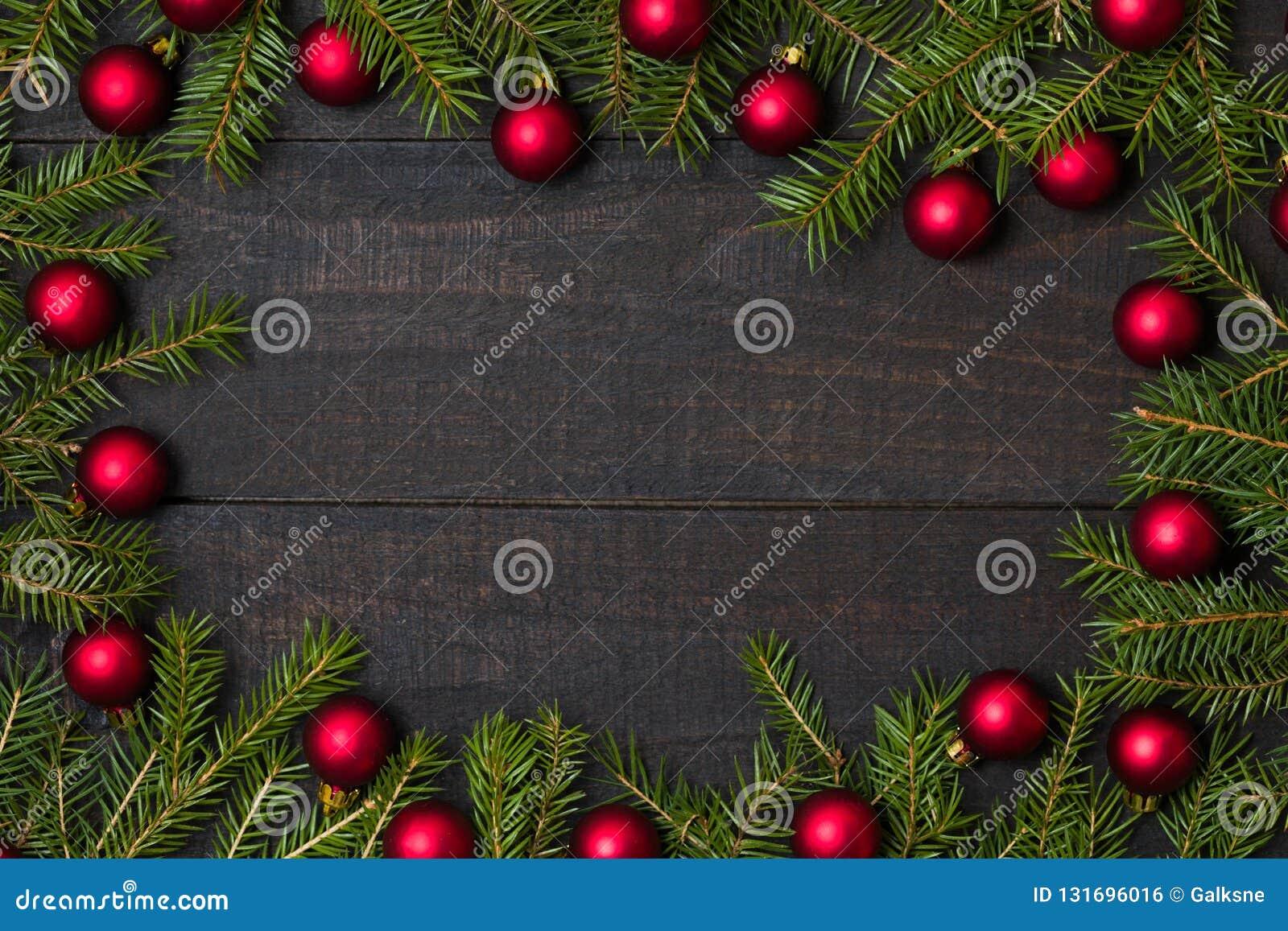 Table en bois rustique foncée flatlay - fond de Noël avec la décoration d ornement de boule et le cadre rouges de branche de sapi