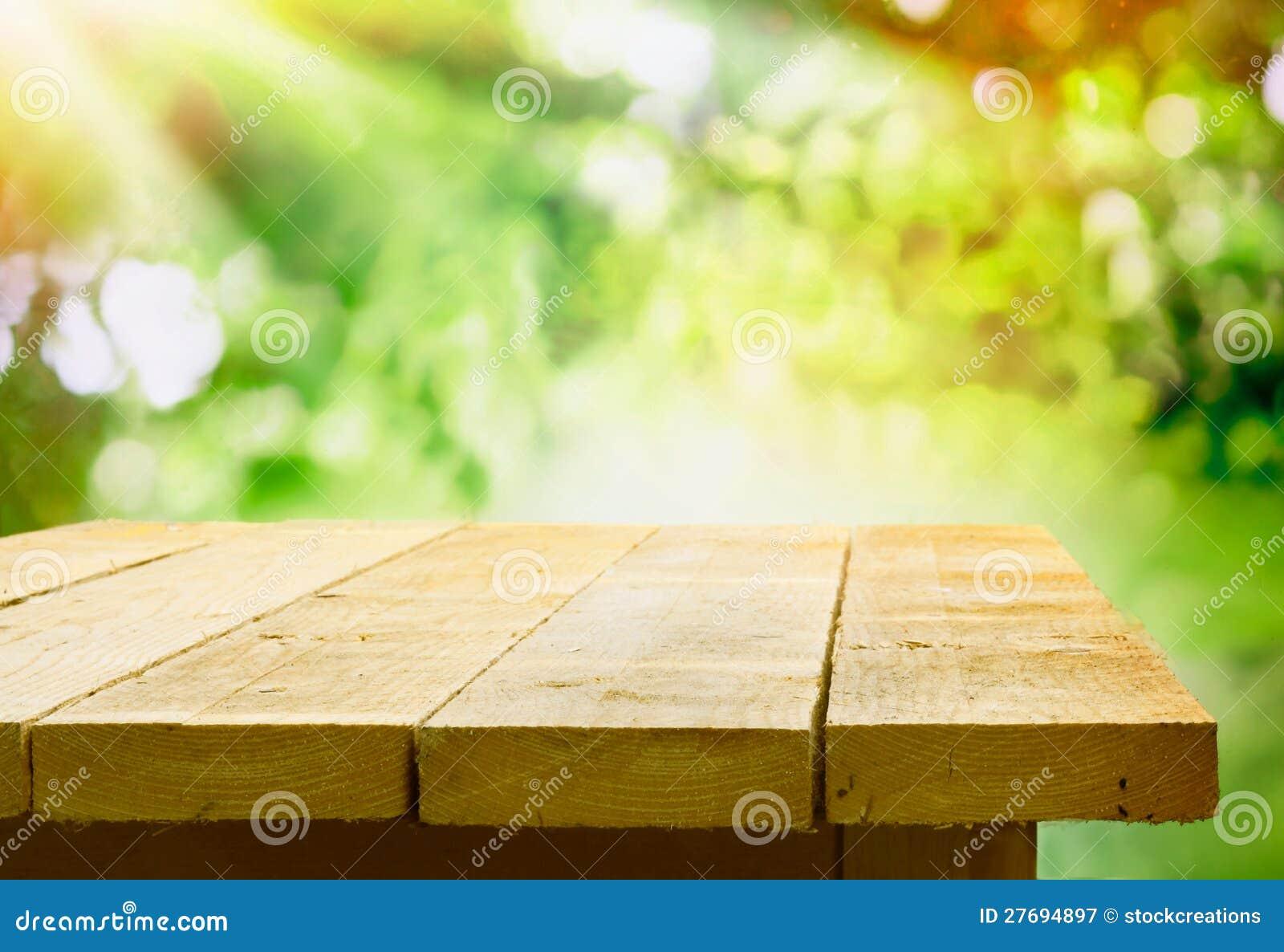 Table en bois vide avec le bokeh de jardin
