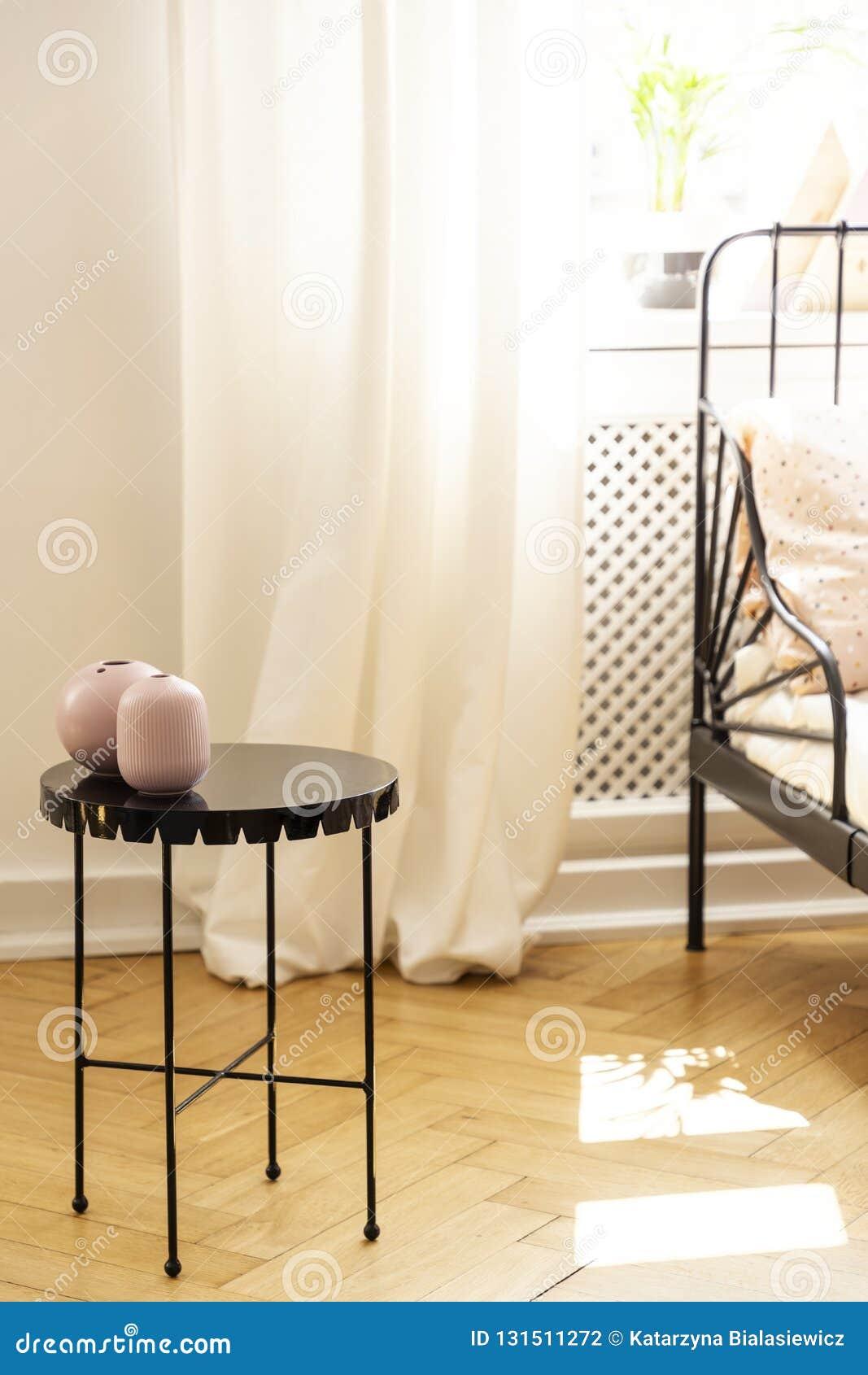 Table en métal avec un vase décoratif dans un intérieur de chambre à coucher