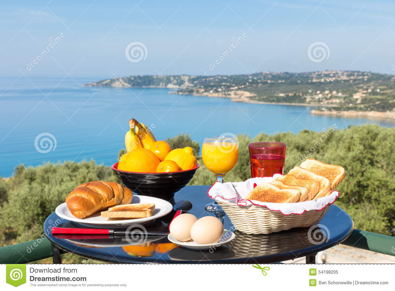 Table with food and drinks in front of blue sea and beach