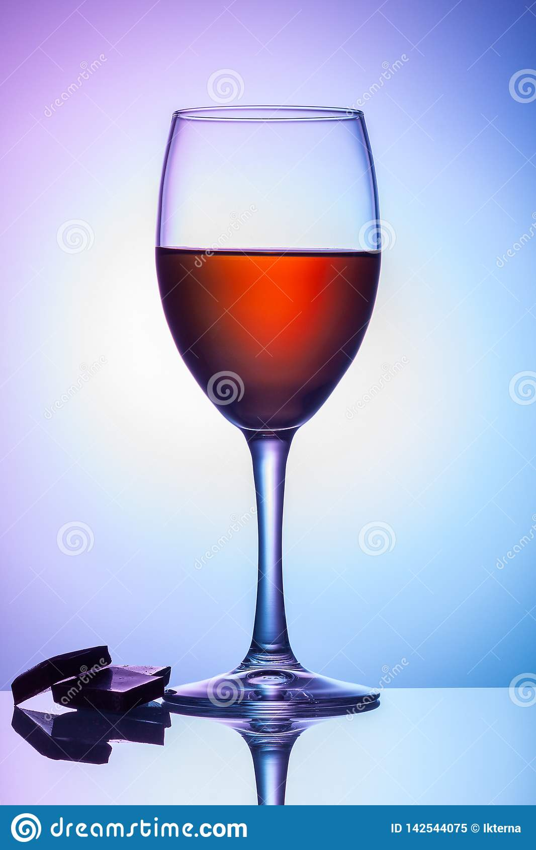 On the table is a glass of wine on a colored background