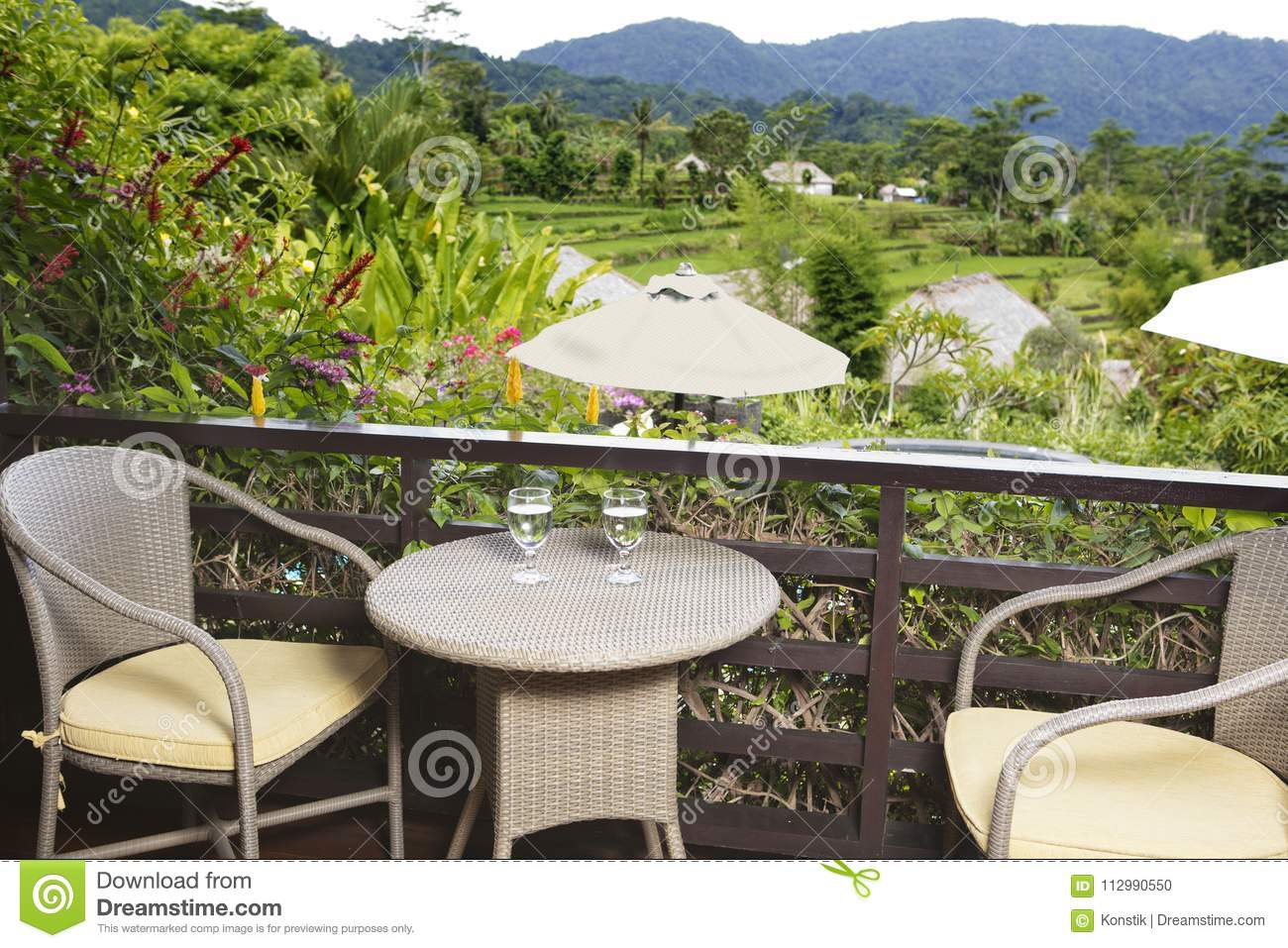 Table with glasses on an open balcony overlooking rice terraces and mountains