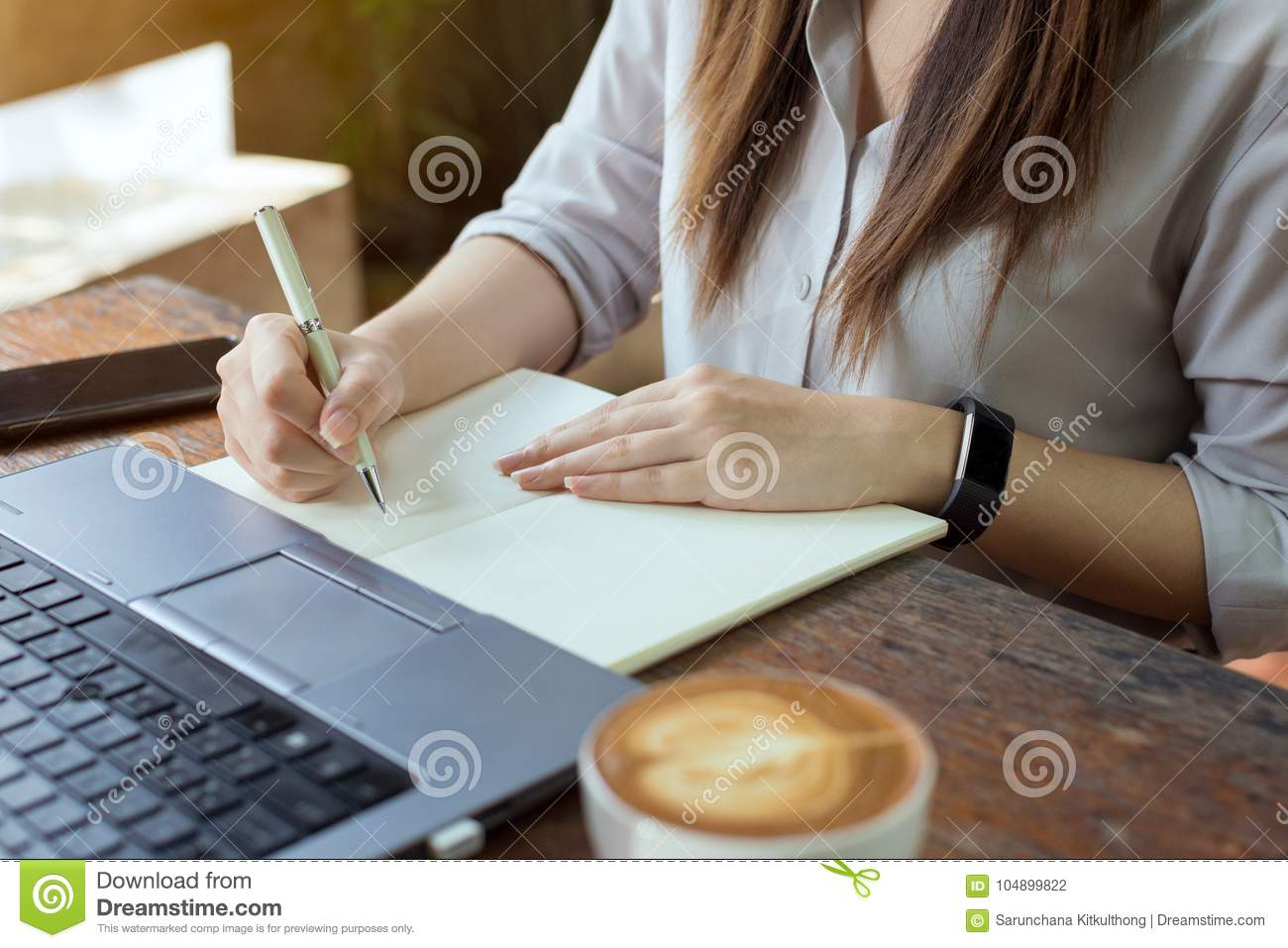 Business women using laptop and note some data on notepad.