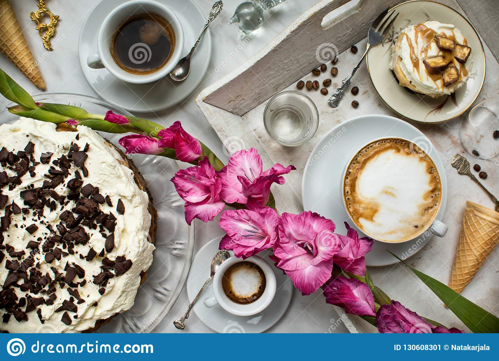 Table with loads of coffee, cakes, cupcakes, desserts, fruits, flowers and croissants. Ancient spoons and a tray,