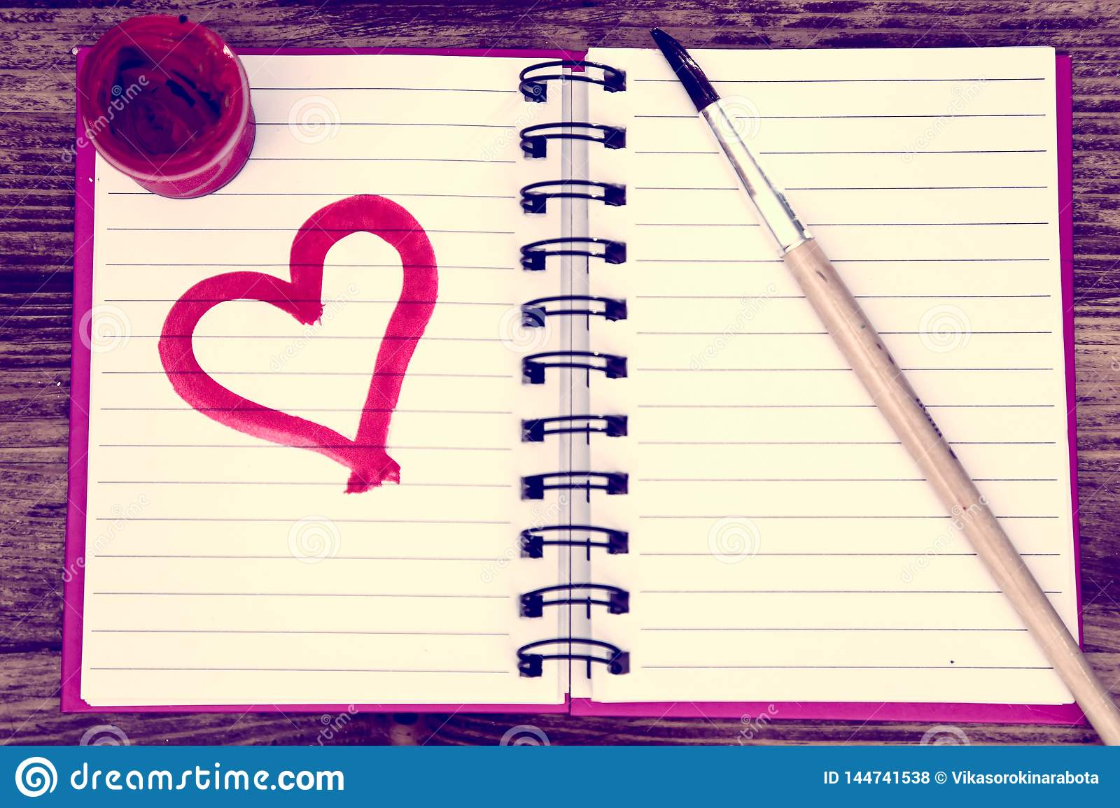On the table is an open pink notebook; a notebook on which is painted with a paint brush and a pink heart