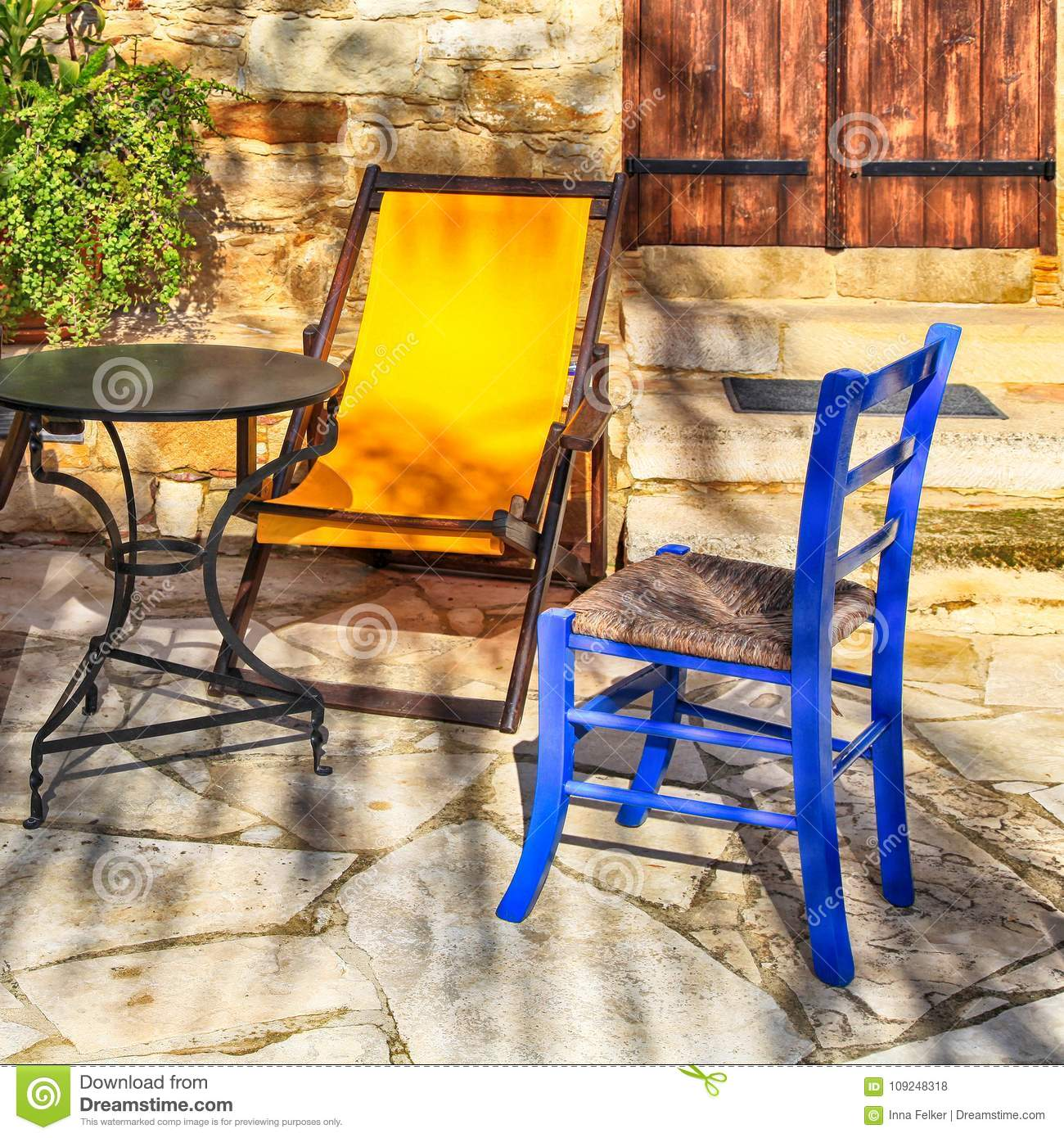 Table and outdoor chairs on terrace with flower pots in beautiful small yard square image