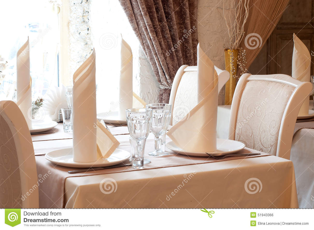 table in restaurant with napkin, decor. beige. stock photo - image