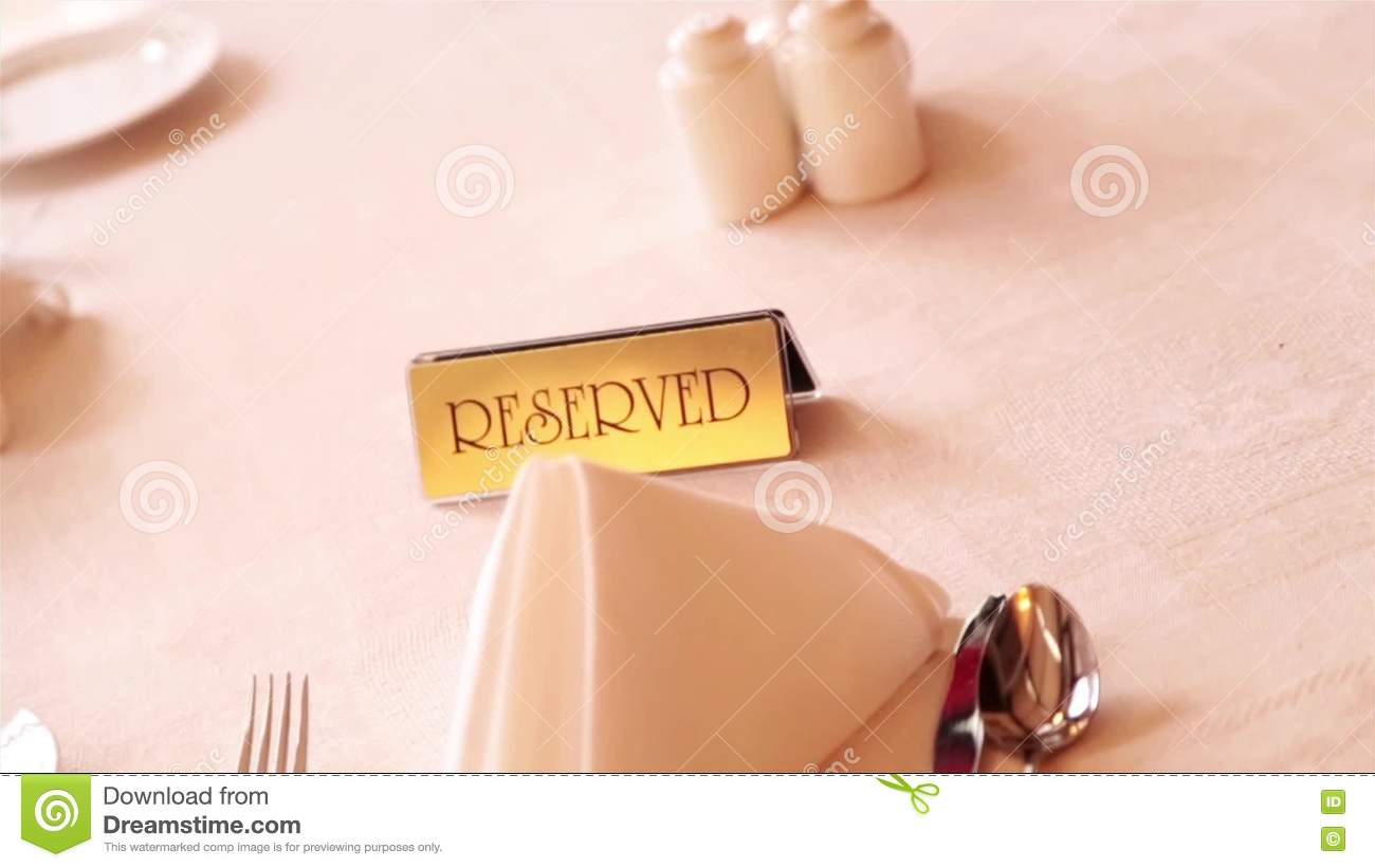 on a table of restaurant with white cloth stands a plaque with the