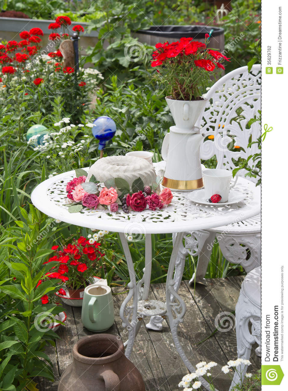 Table Set In Garden With Flowers All Around Stock