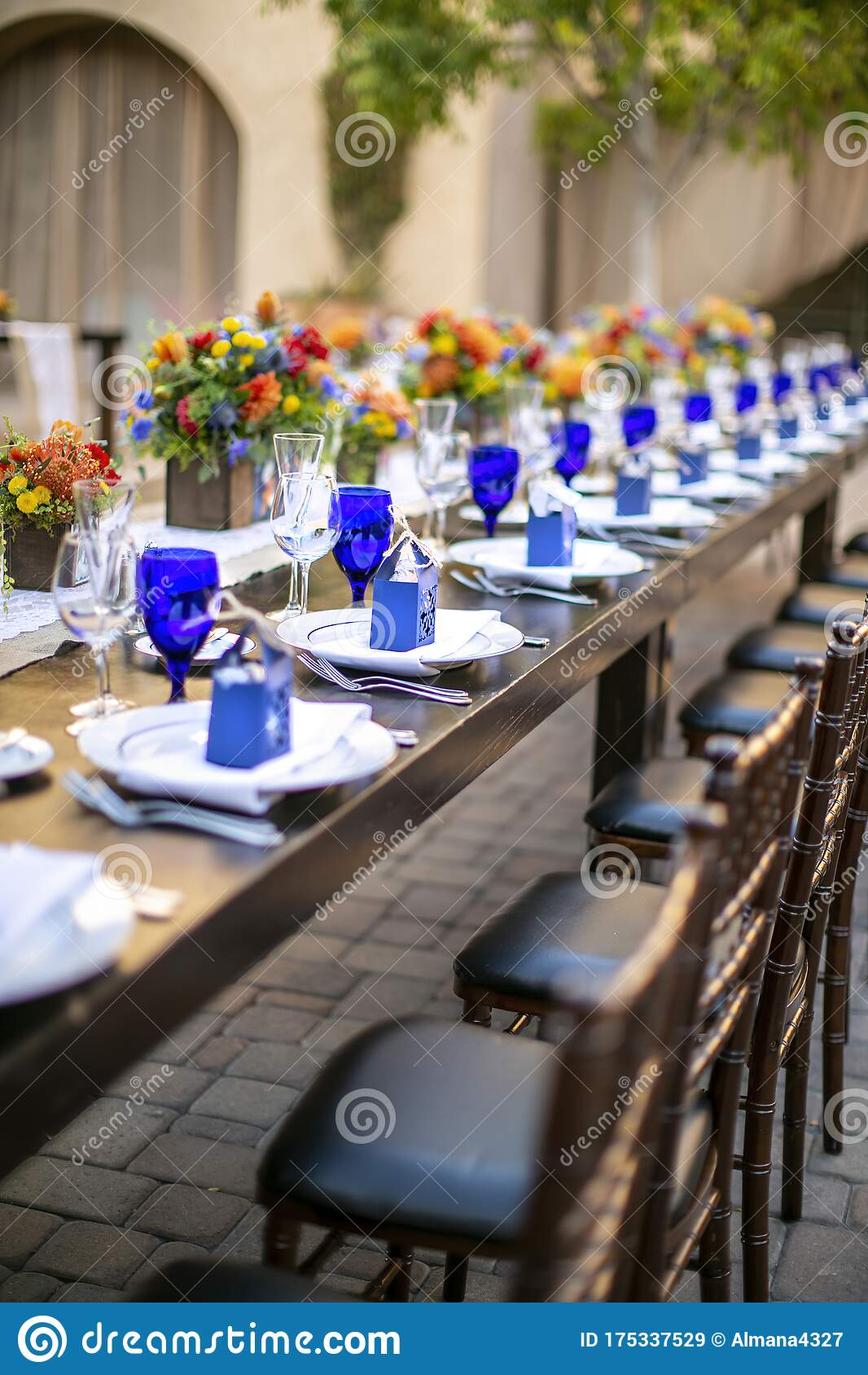 Table Setting For A Wedding Celebration In An Outdoor Mission Style Patio With Blue And Orange Theme And Flower Decorations Stock Image Image Of Dinner Mission 175337529