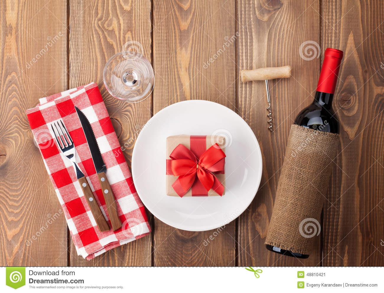 Table Setting With Gift Box On Plate Wine Glass And Red