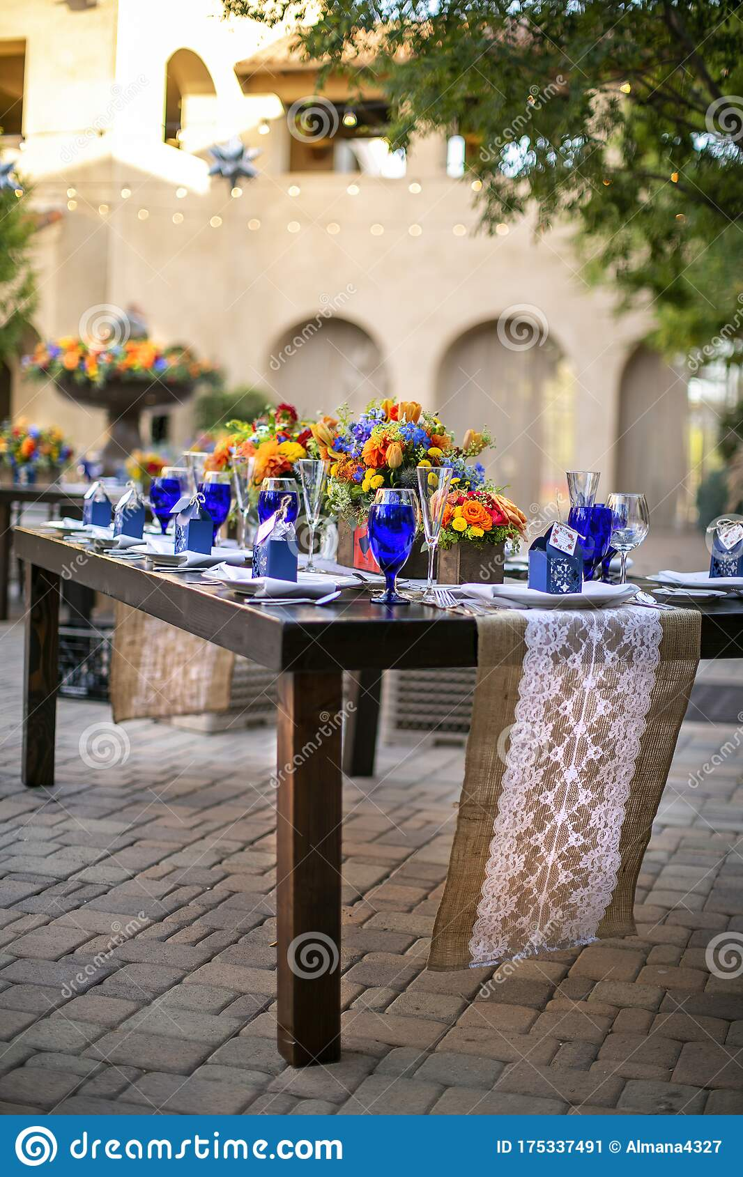 Table Setting For A Wedding Celebration In An Outdoor Mission Style Patio With Blue And Orange Theme And Flower Decorations Stock Image Image Of Ceremony Bouquet 175337491