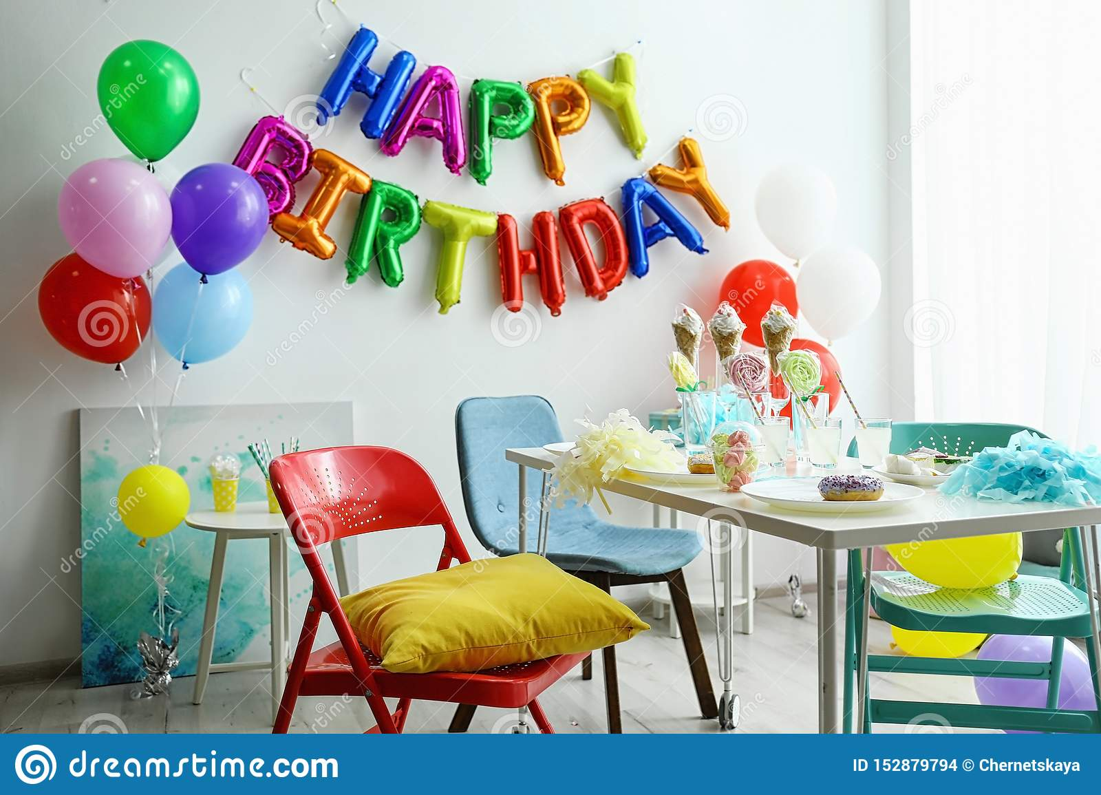 Table with treats and phrase HAPPY BIRTHDAY made of colorful balloon letters