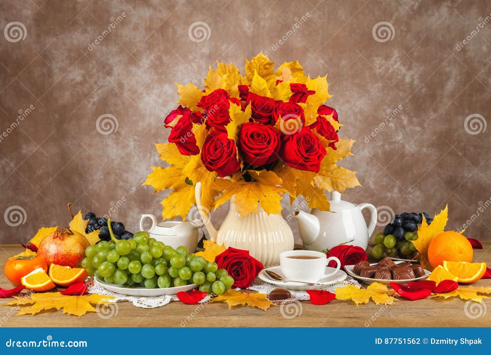 Tableau avec des tasses de thé, de chocolats et de roses d un bouquet