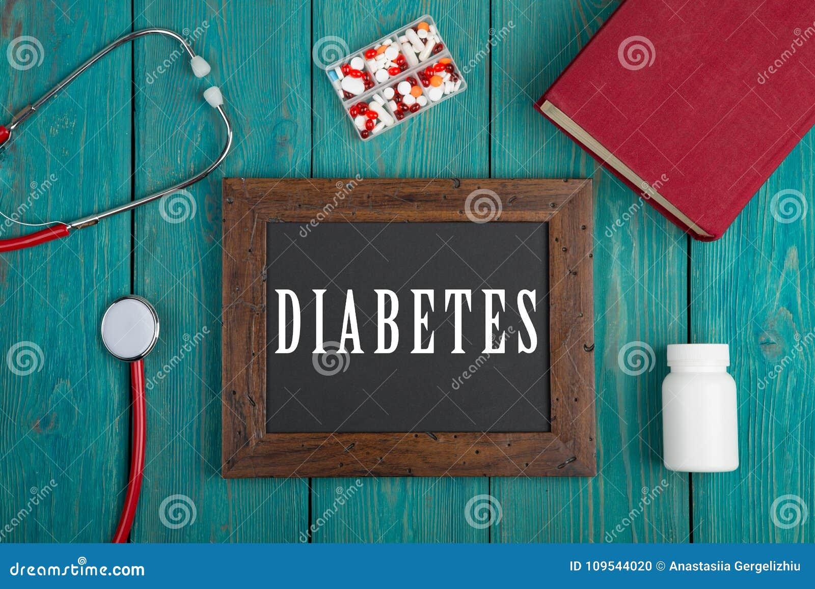 Tableau noir avec le texte et le x22 ; Diabetes& x22 ; , stéthoscope, pilules et livre sur le fond en bois bleu