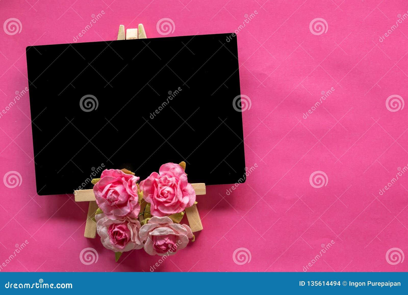 Tableau noir vide et fleur rose sur le fond rose avec l espace de copie, concept de jour de valentines