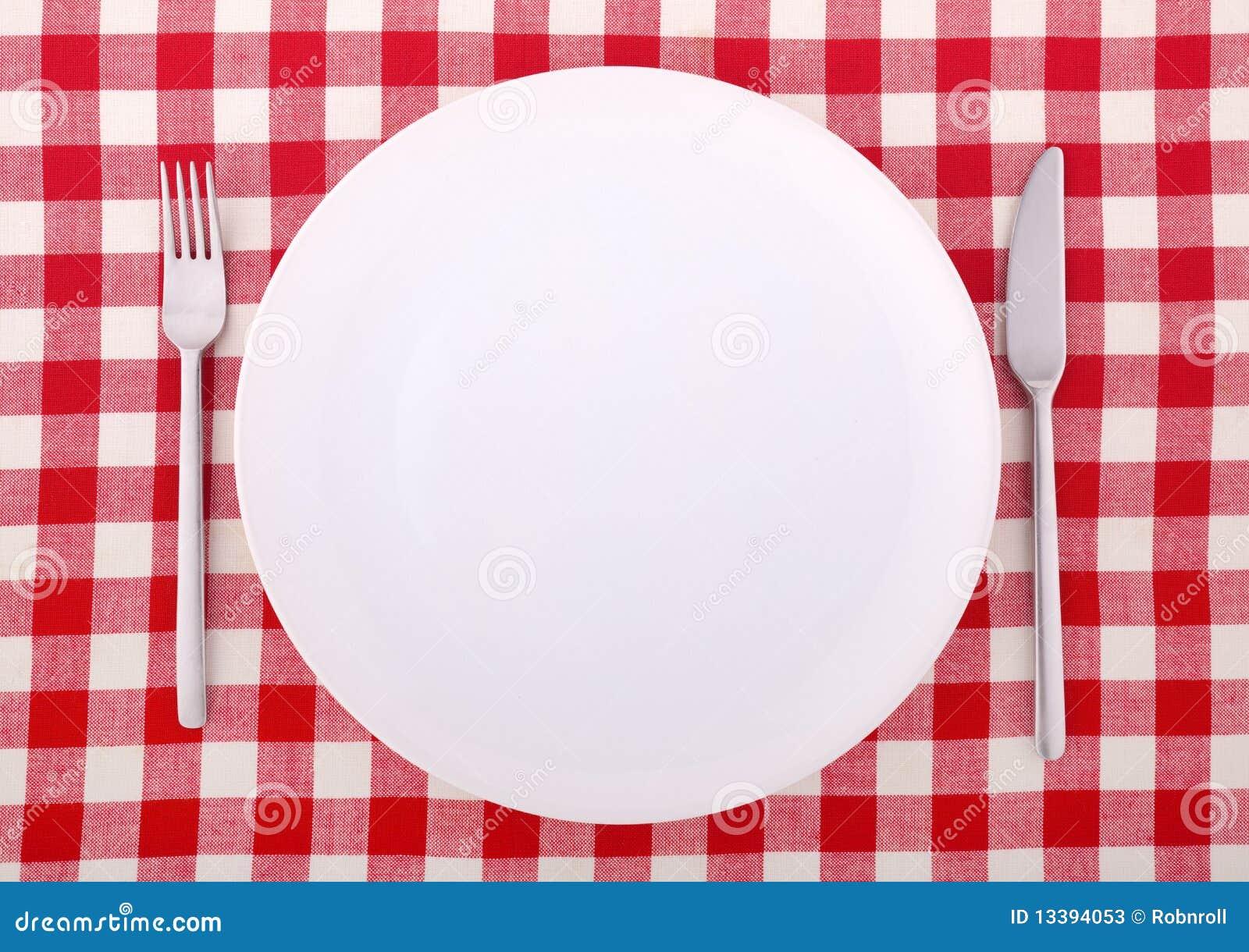 Tablecloth com forquilha, faca e uma placa vazia